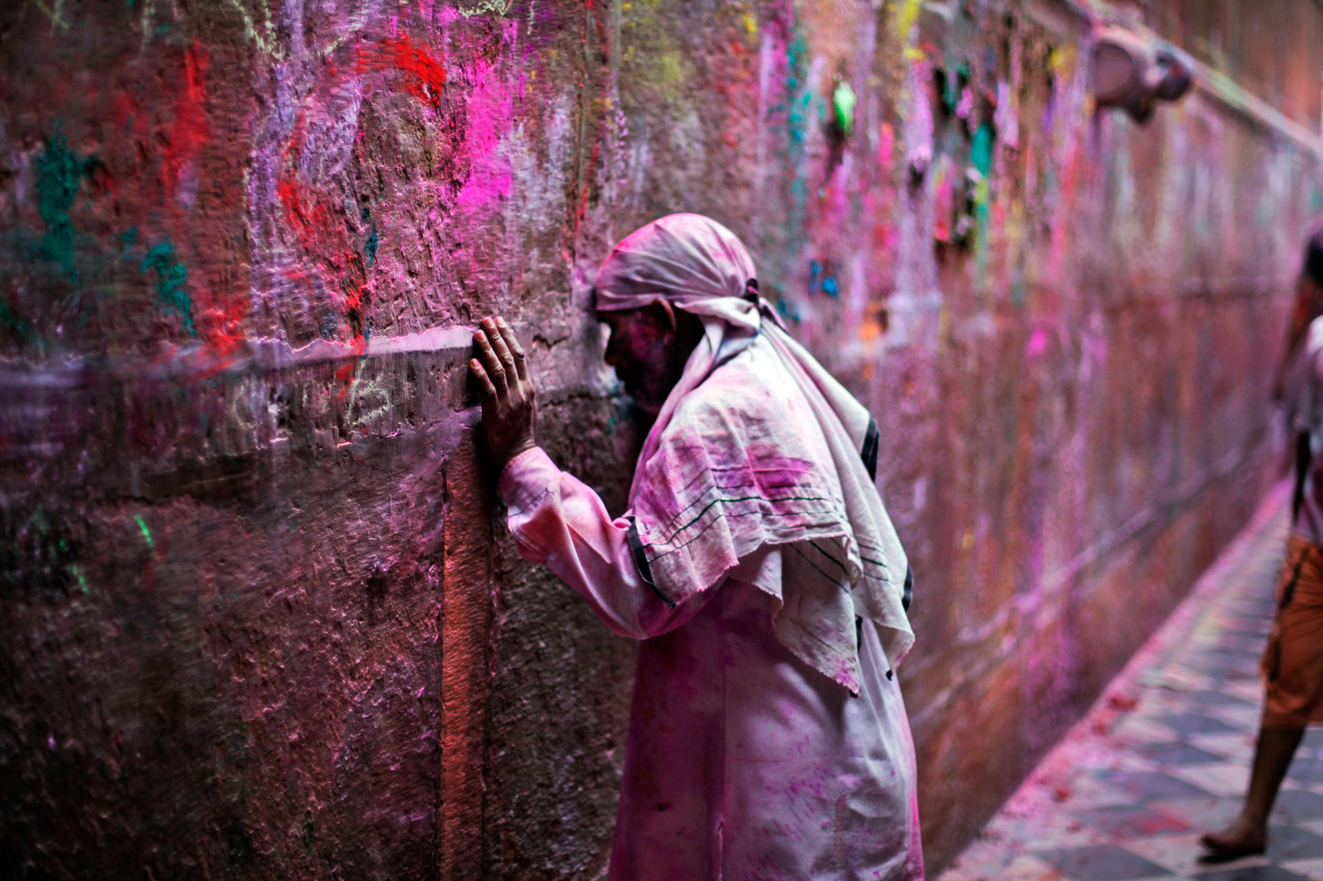 An Indian devotee rests his forehead in an act of respect on the wall of the Banke Bihari temple during Holi celebrations in Vrindavan, India, on March 27, 2013.