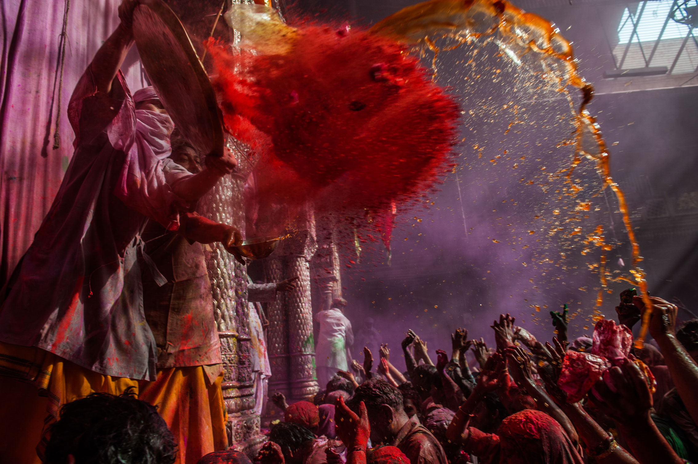 A Hindu priest throws coloured powder at devotees during Holi festival, at the Banke Bihari temple, on March 3, 2013.