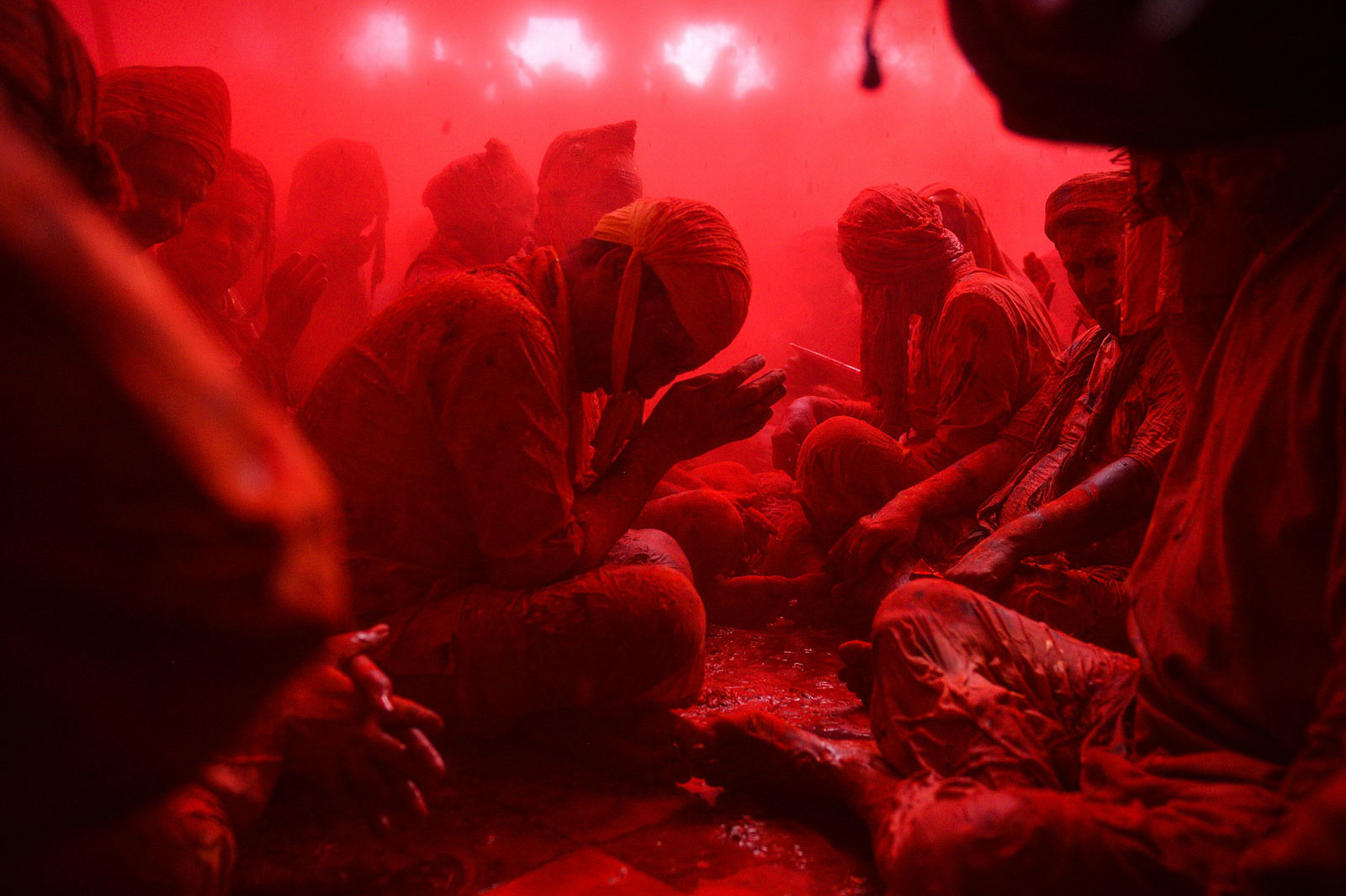 An Indian reveler covered in colored powder sits inside a temple as he and other prays during the Lathmar Holi celebrations in the village of Barsana, on March 17, 2016.