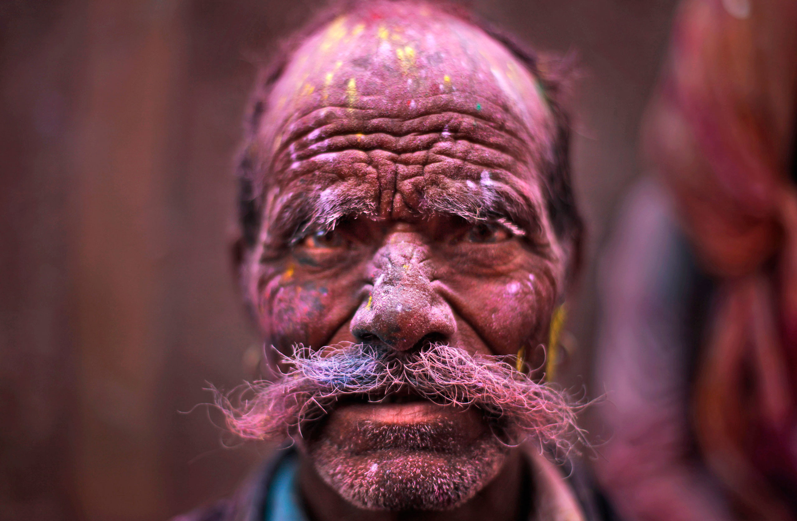 A Hindu devotee, face smeared with colored powder, leaves the Banke Bihari temple during Holi celebrations in Vrindavan, on, March 27, 2013.
