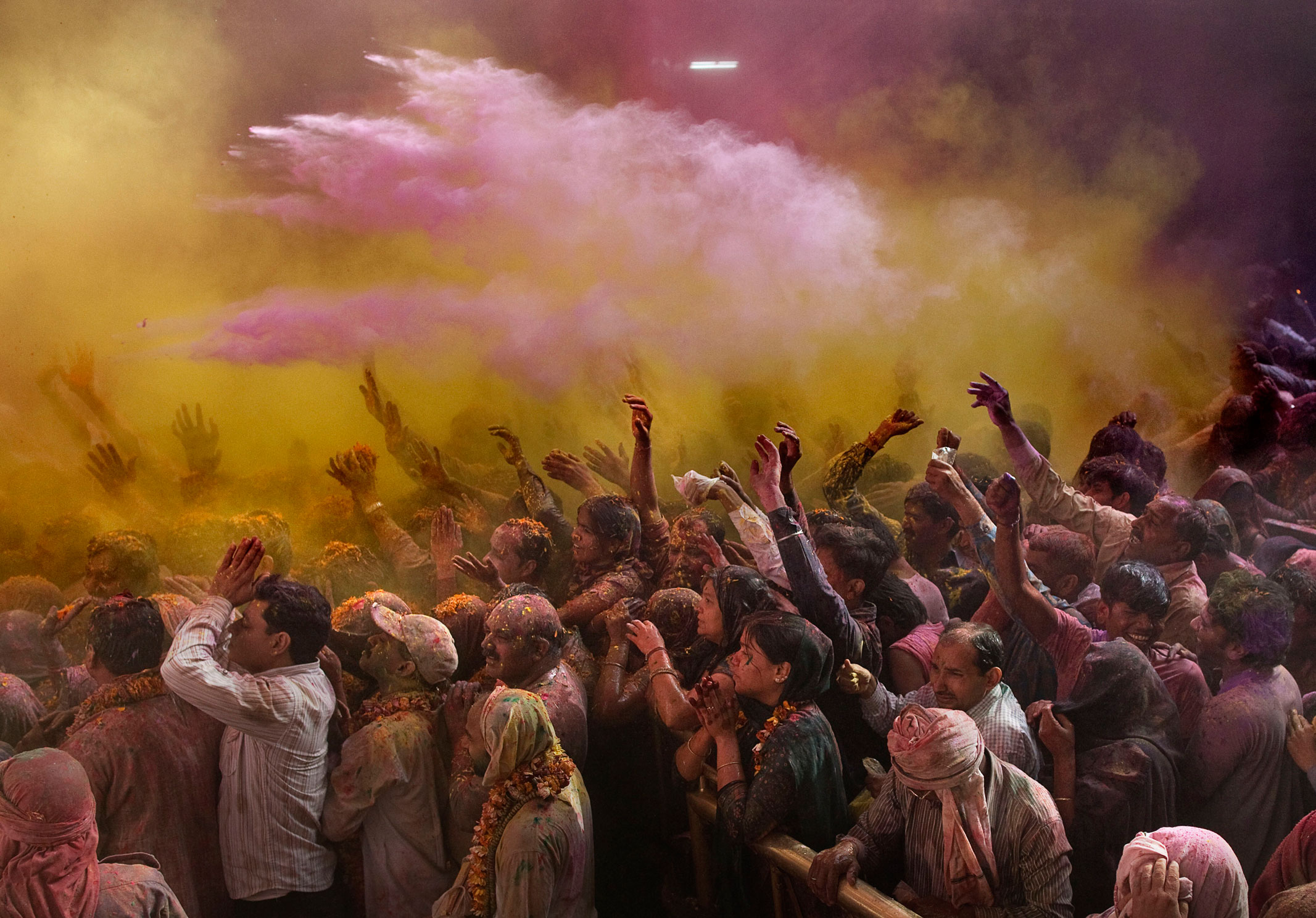 Hindu devotees pray and face a deity as colored powder is thrown on them while celebrating  Holi,  the festival of color, crowd at the Banke Bihari temple in Vrindavan, on March 7, 2012.