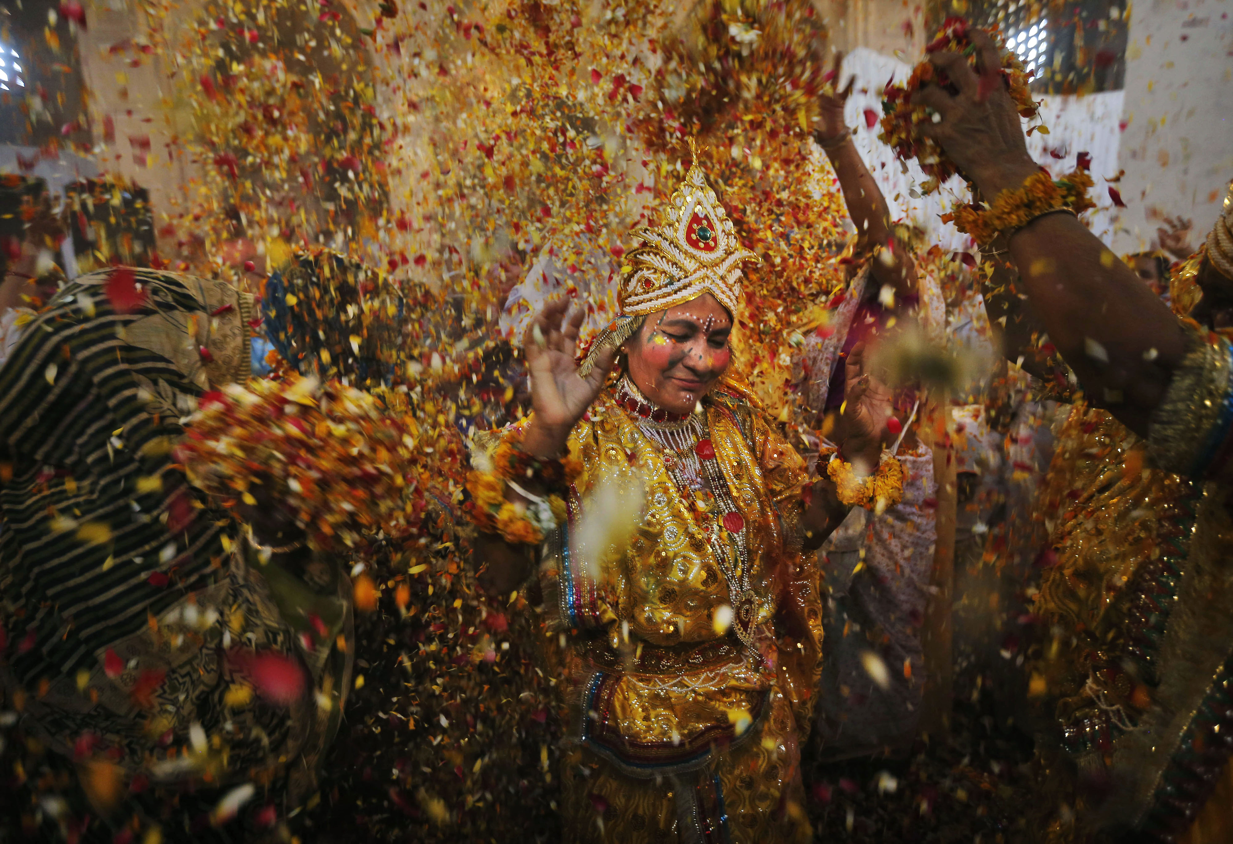 An Indian widow dressed as a consort of Lord Krishna walks as others throw flowers during Holi celebrations in Vrindavan, on March 24, 2013.