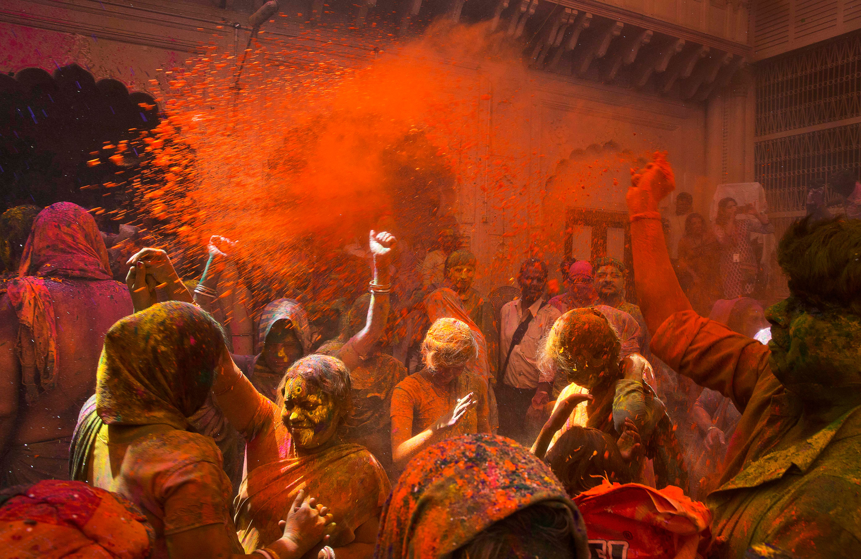 Locals and Indian Hindu widows throw flower petals and colored powder during Holi celebrations at the Gopinath temple, south-east of New Delhi, on March 21, 2016.