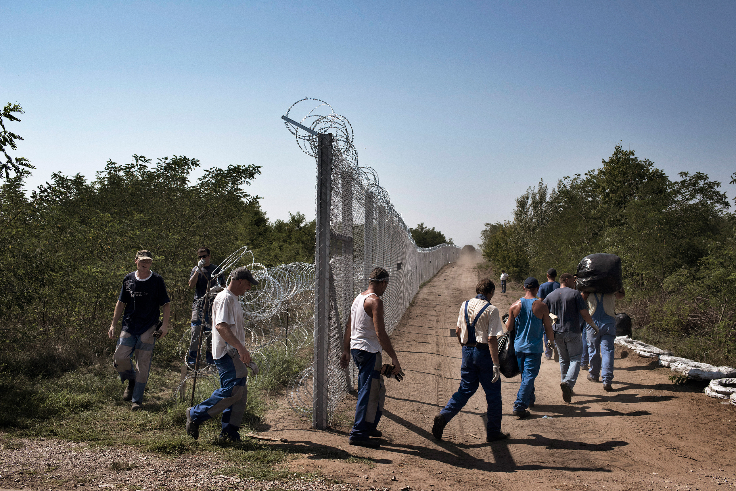Local workers build up a fence to guard against migrants in Ásotthalom, Hungary, September 2015.