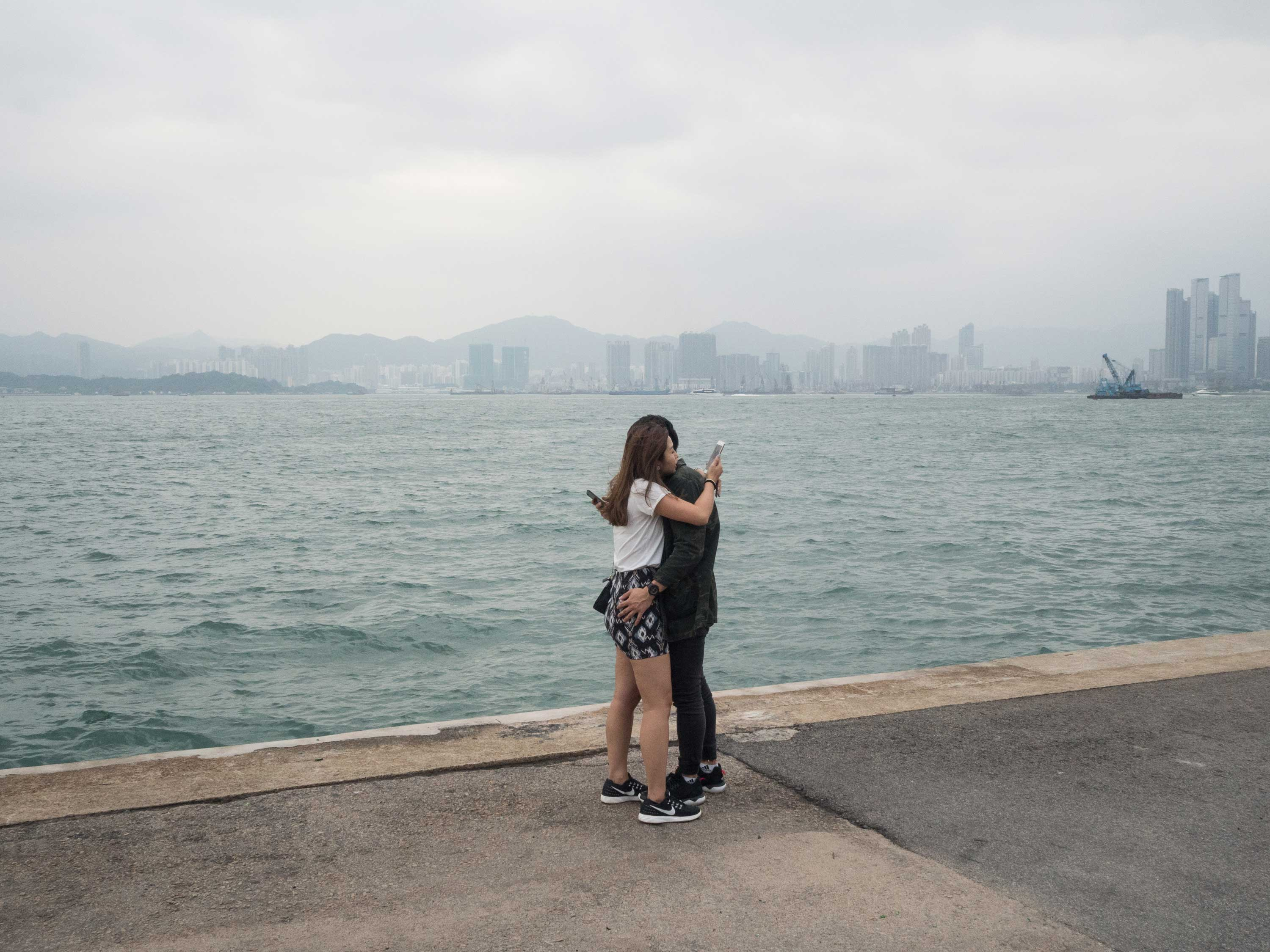 Two young lovers embrace while checking their phones in Hong Kong.