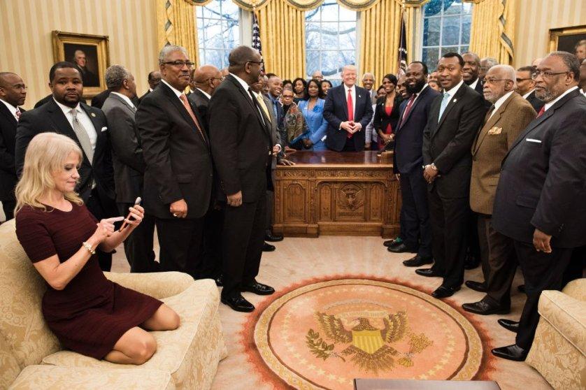 Kellyanne Conway (L) checks her phone after taking a photo as President Donald Trump and leaders of historically black universities and colleges pose for a group photo in the Oval Office of the White House on Feb. 27, 2017 in Washington, DC.