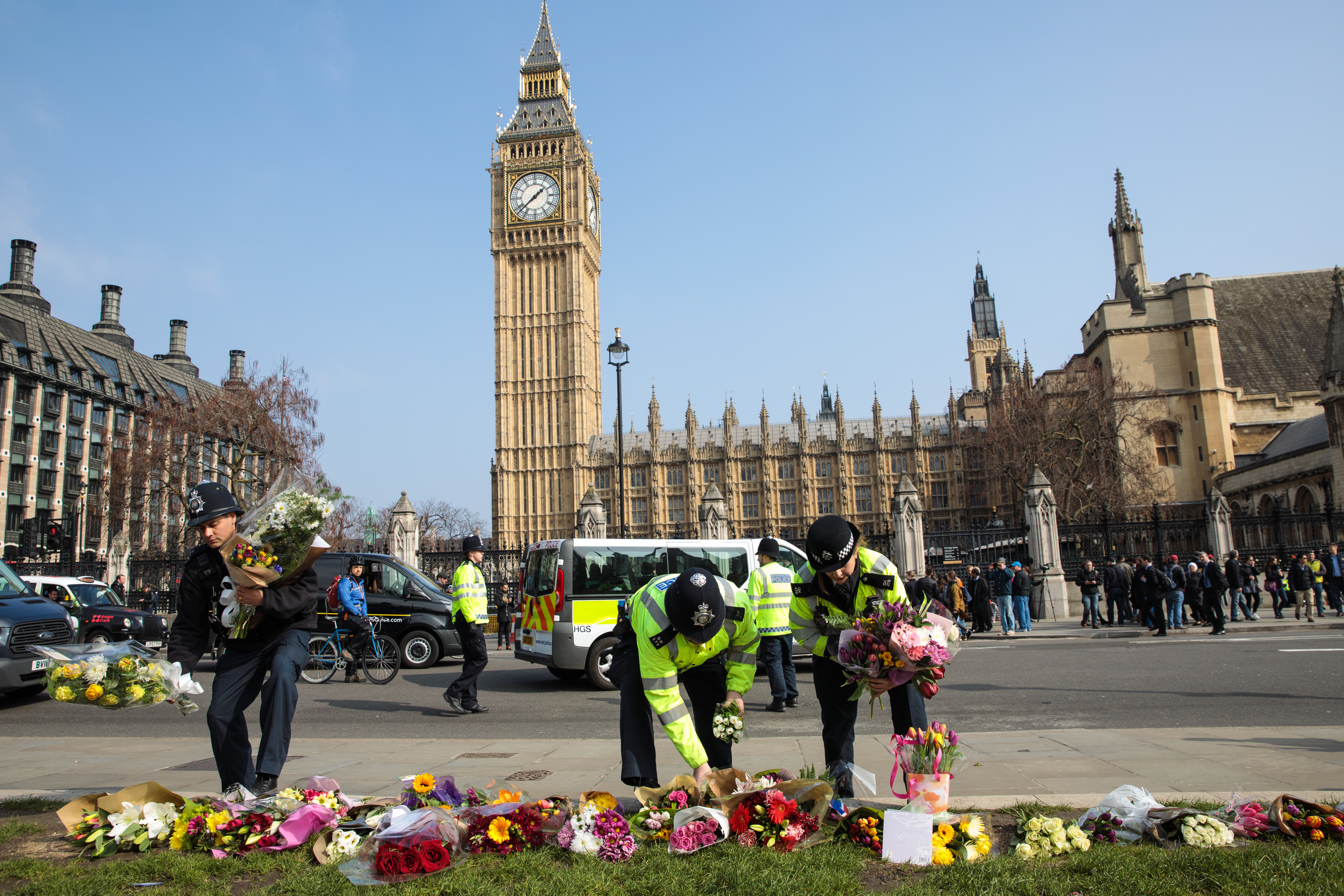 Police officers move floral tributes from outside the Houses of Parliament to Parliament Square after the March 22, 2017, attack on Westminster in London