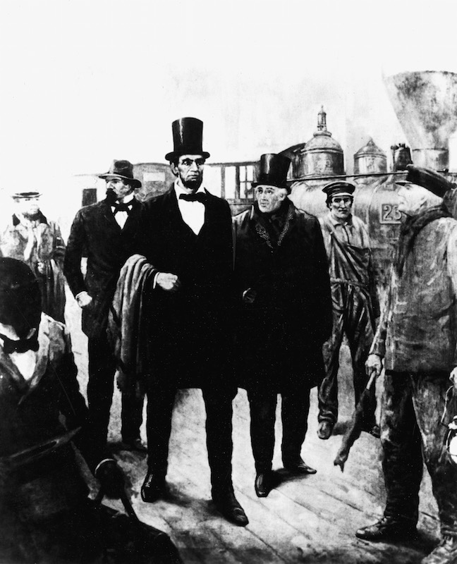 An illustration of American President-elect Abraham Lincoln (1809 - 1865) walking near a railroad with detective Allan PInkerton on Feb. 23, 1861. The Pinkerton National Detective Agency foiled a plot to assassinate Lincoln that year.