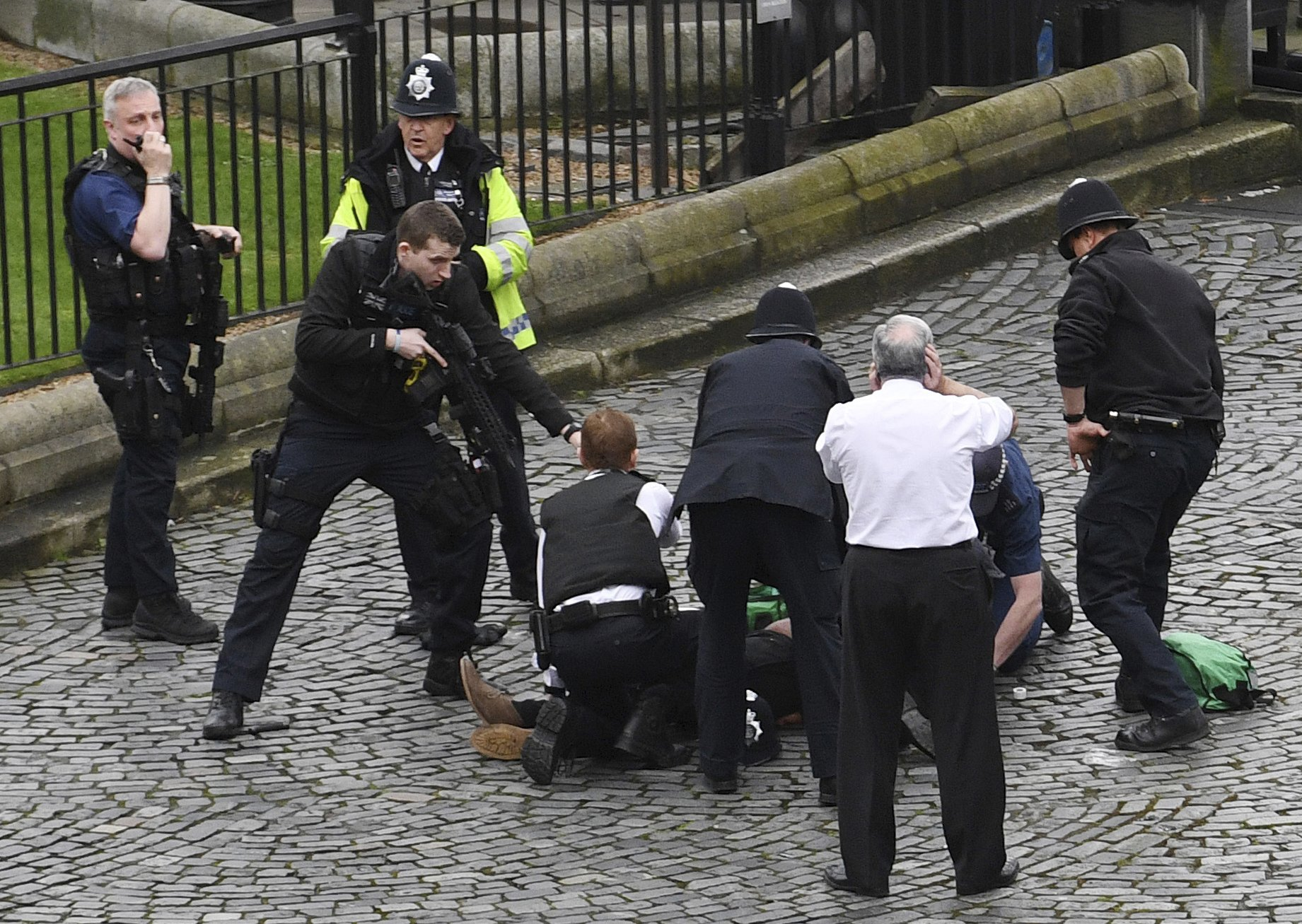 A policeman points a gun at a man on the floor as emergency services attend the scene outside the Palace of Westminster, on March 22, 2017.
