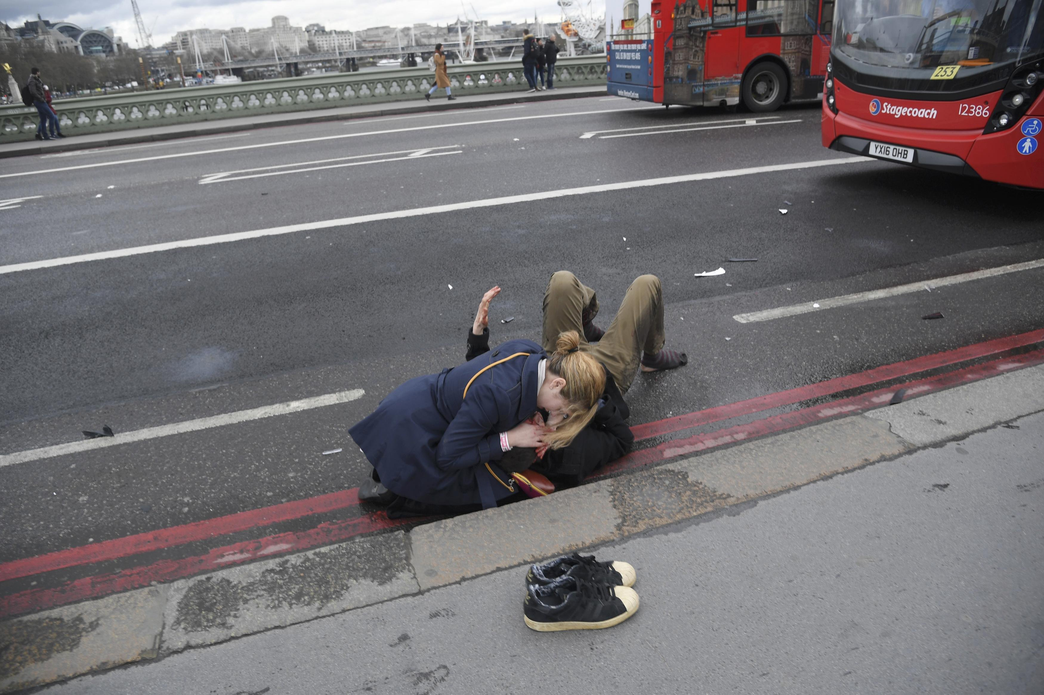A woman assist an injured person after an incident on Westminster Bridge, on March 22, 2017.