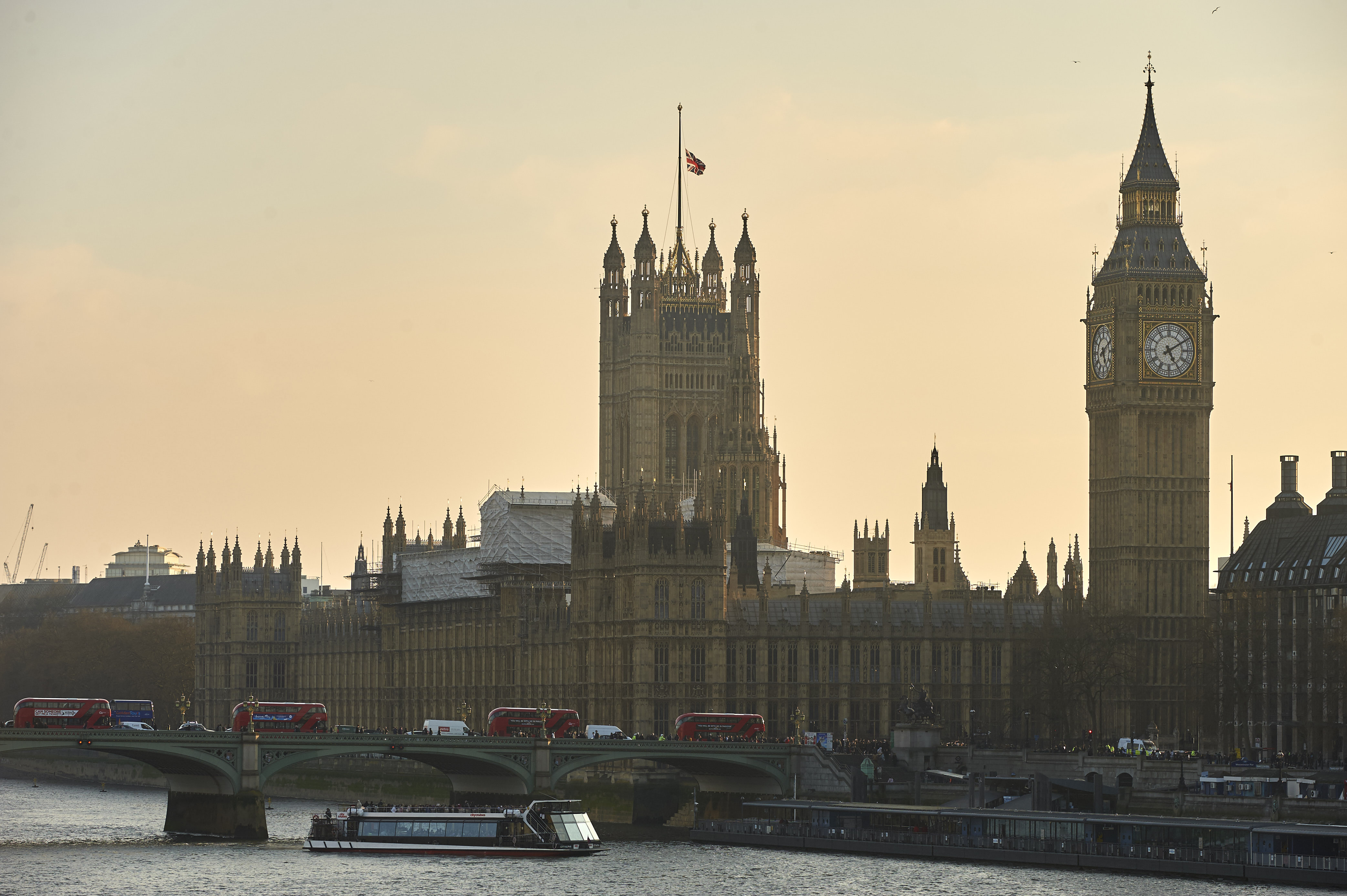A picture shows red London buses, pedestrians and traffic crossing Westminster Bridge over the River Thames with the Union flag atop the Houses of Parliament (R) flying at half-mast in central London on March 23, 2017.