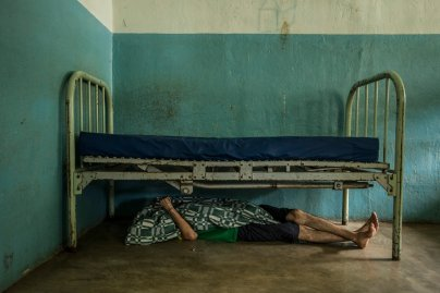 Raul Martinez, who has little medication for his schizophrenia, takes a nap under his bed at the state-run Pampero Psychiatric Hospital in Barquisimeto, Venezuela, on July 28, 2016.