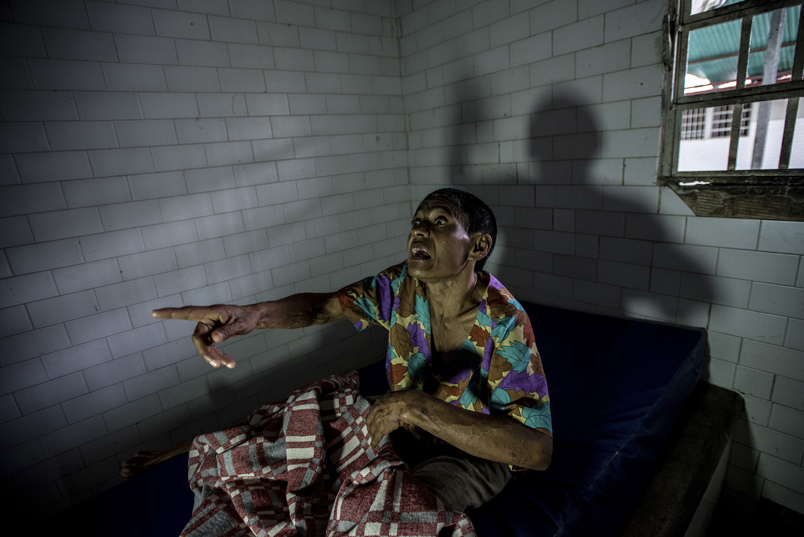 Margarita Silva, a paranoid schizophrenic, yells at nurses from her solitary confinement cell, where she was being held after biting off another patient's nose and eating it, at the state-run Pampero Psychiatric Hospital in Barquisimeto, Venezuela, on Aug. 24, 2016.