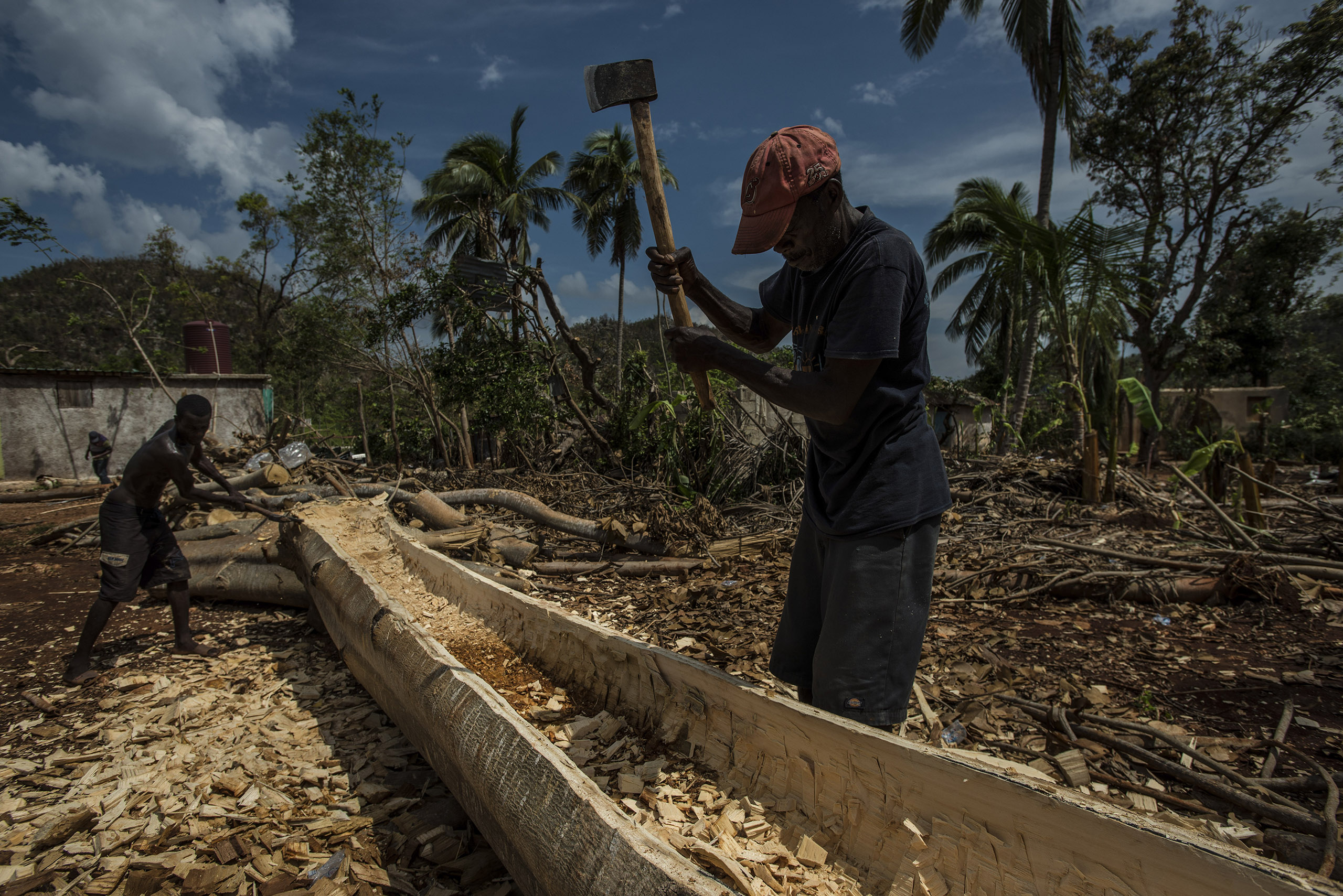 Men make a dugout canoe from a tree felled by Hurricane Matthew in Pestel, Haiti, on Oct. 16, 2016. Like much of the country's southern peninsula, Pestel is writhing beneath the weight of disaster.