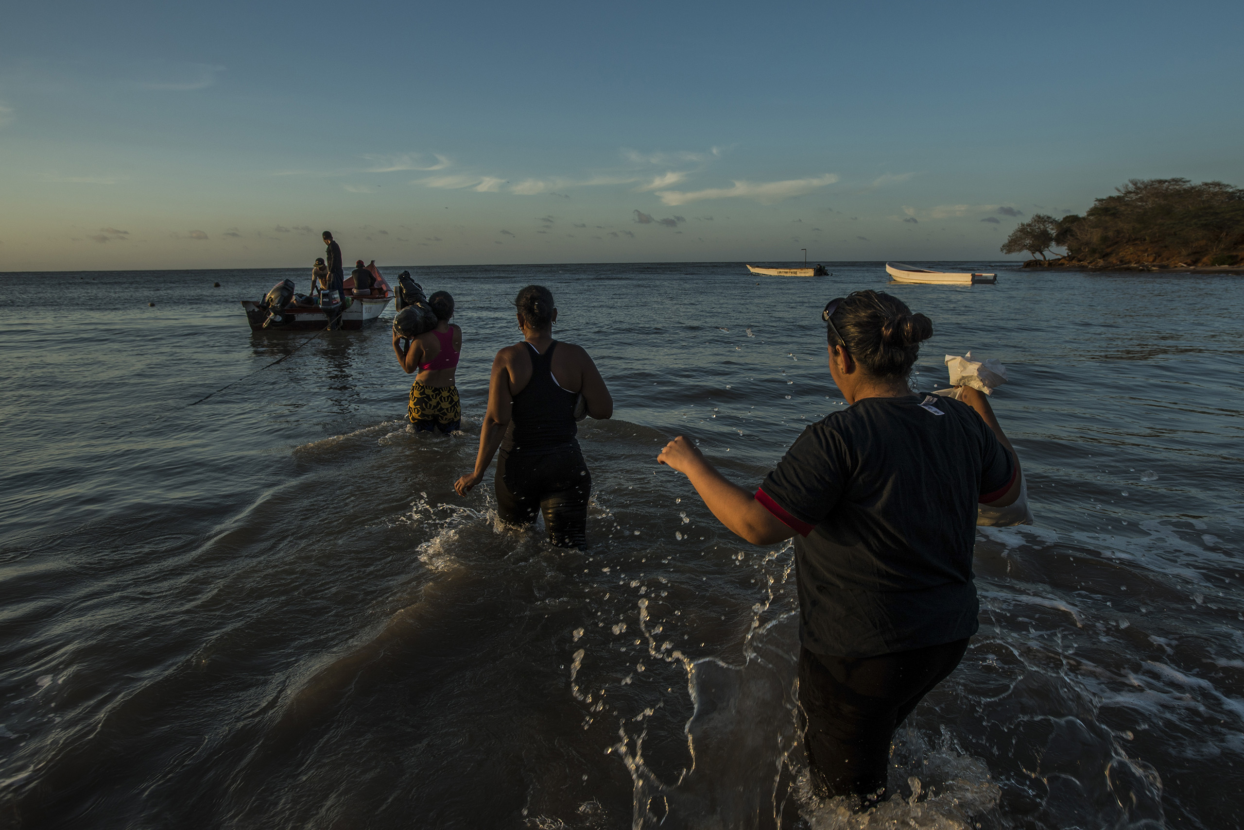 Migrants board a smuggler's boat that will take them to the Caribbean island of Curacao on Sept. 26, 2016. More than 150,000 people have fled the economic collapse in Venezuela in the last year alone, the most in more than a decade, scholars say, with the sea route posing special dangers.