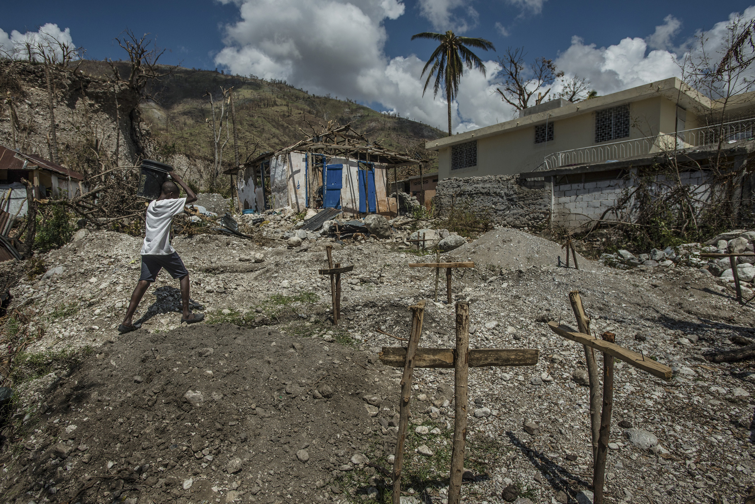 A boy carries river water to what remains of his family's home, destroyed by Hurricane Matthew, in Rendel, Haiti, on Oct. 12, 2016.