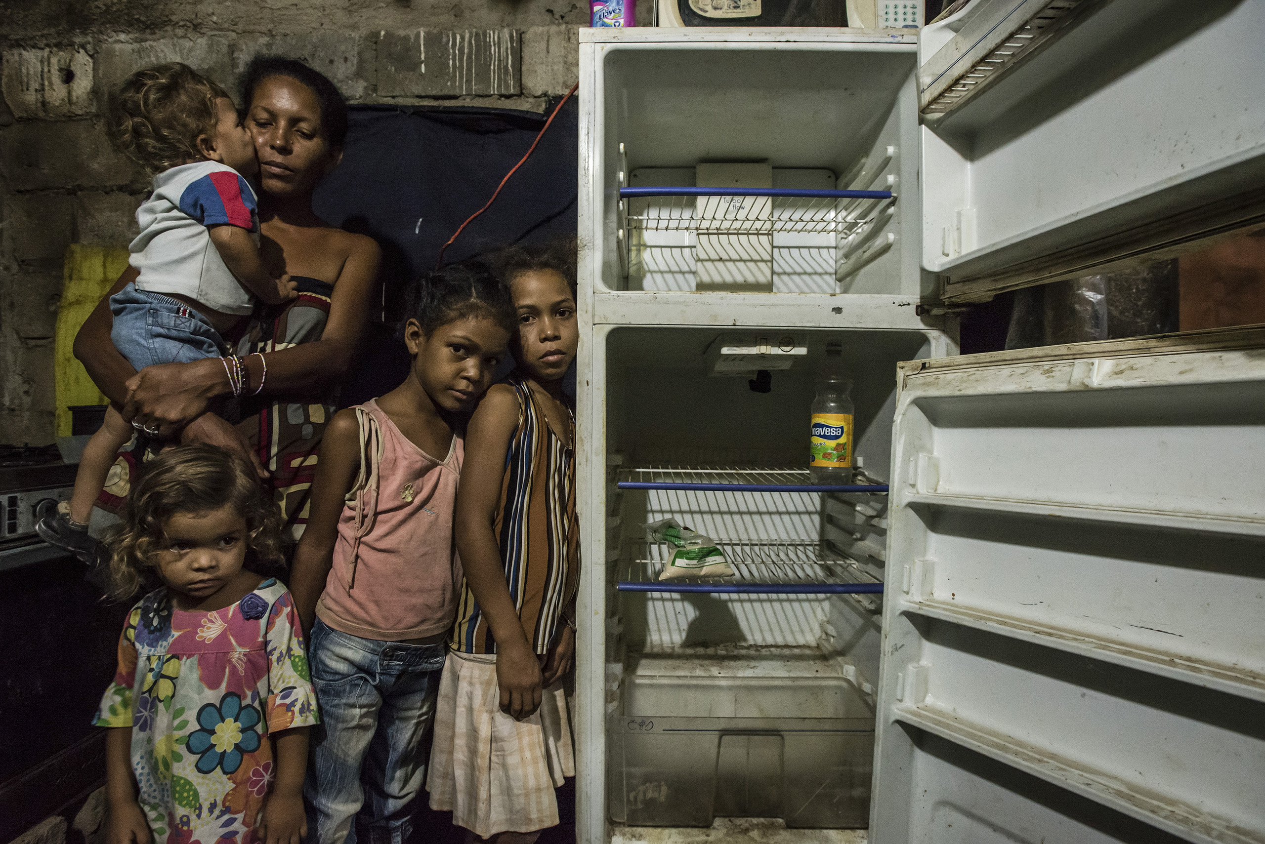 Leidy Cordova, 37, with four of her five children at their home in Cumana, Venezuela, on June 16, 2016. Their broken refrigerator held the only food in the house: a bag of corn flour and a bottle of vinegar.