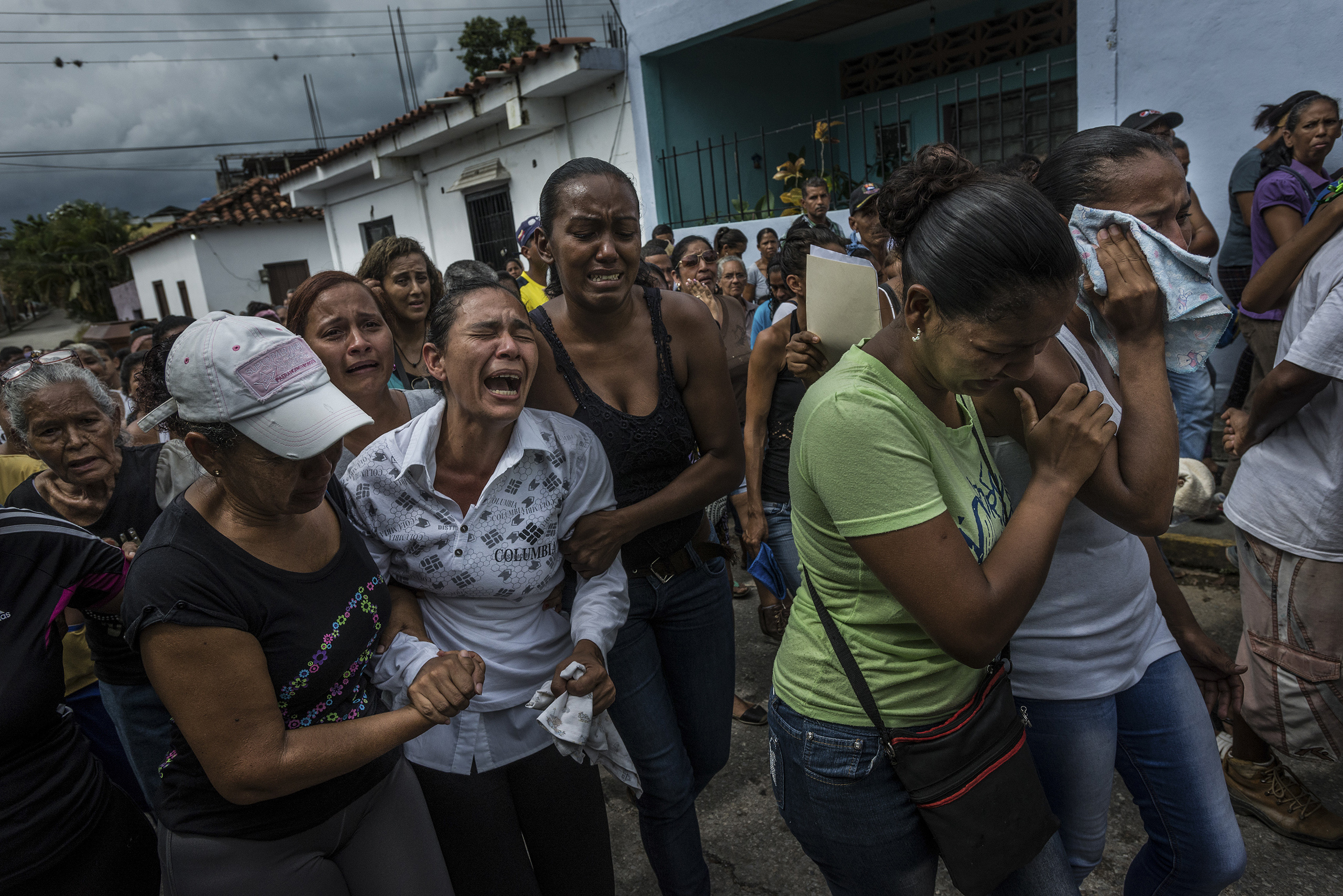 People mourn during a group funeral procession and memorial for four men, who were tortured and killed by the Venezuelan army, in the town of Capaya on Nov. 29, 2016. Throughout the country, armed military forces have become Venezuela's lawkeepers, engaging in commando-style raids that sometimes take on the profile of urban warfare.