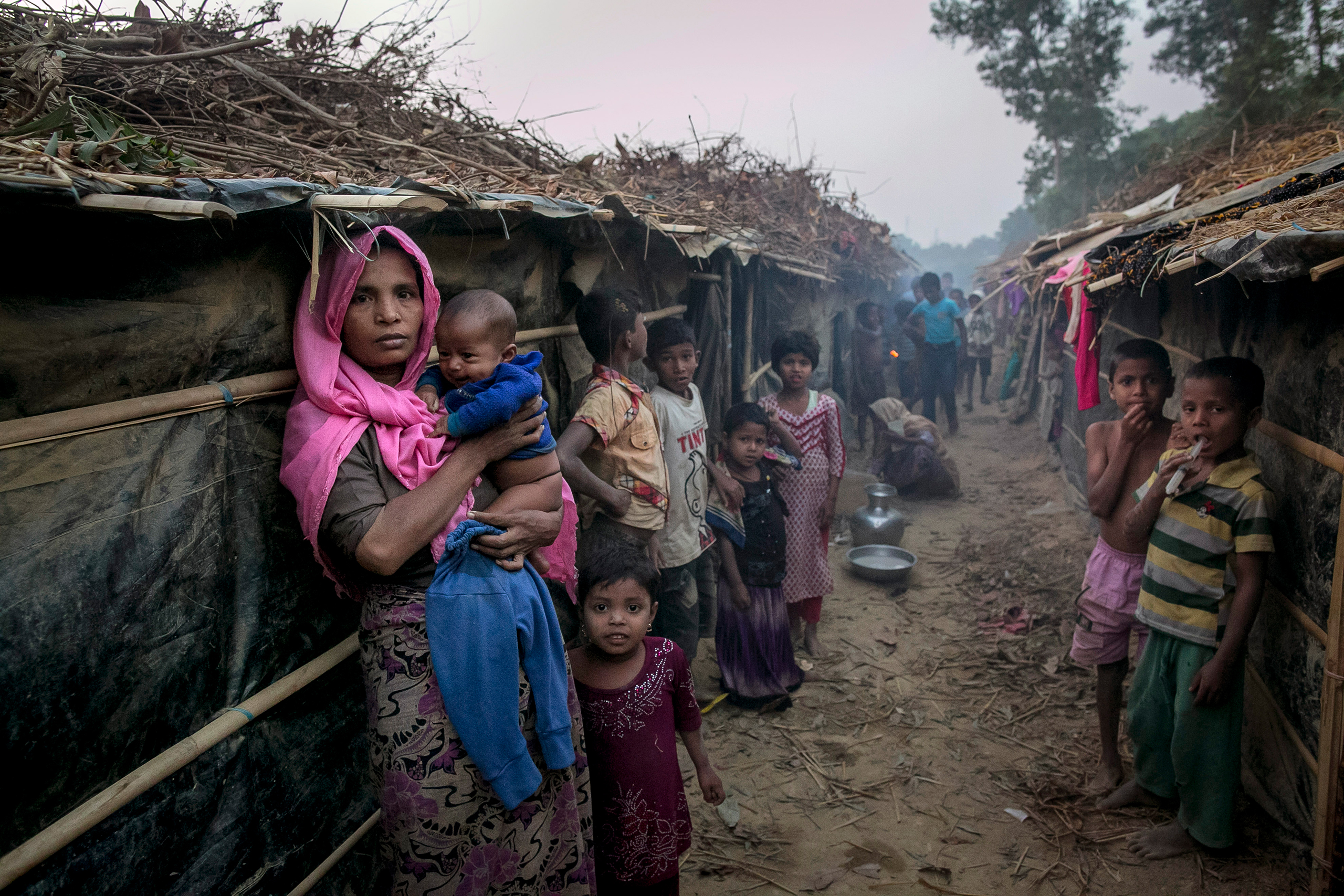 People stand outside their shelters in the Kutapalong Rohingya refugee camp in Cox's Bazar, Bangladesh, on Feb. 8, 2017