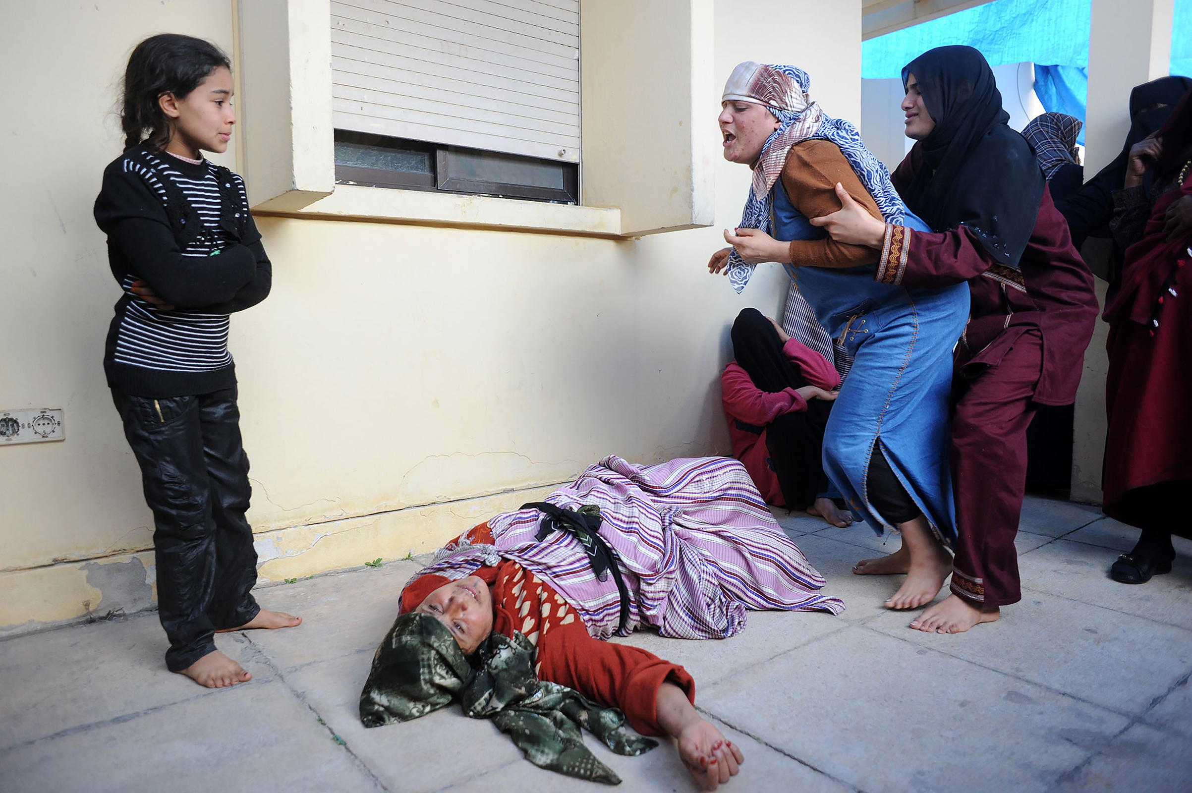 Mobarak Mohamed, 46, lies distraught on hearing the news that her son Hassan Ali, 14 had been killed by Gaddafi's forces during the first Battle of Brega, March 2 2011. Libya.