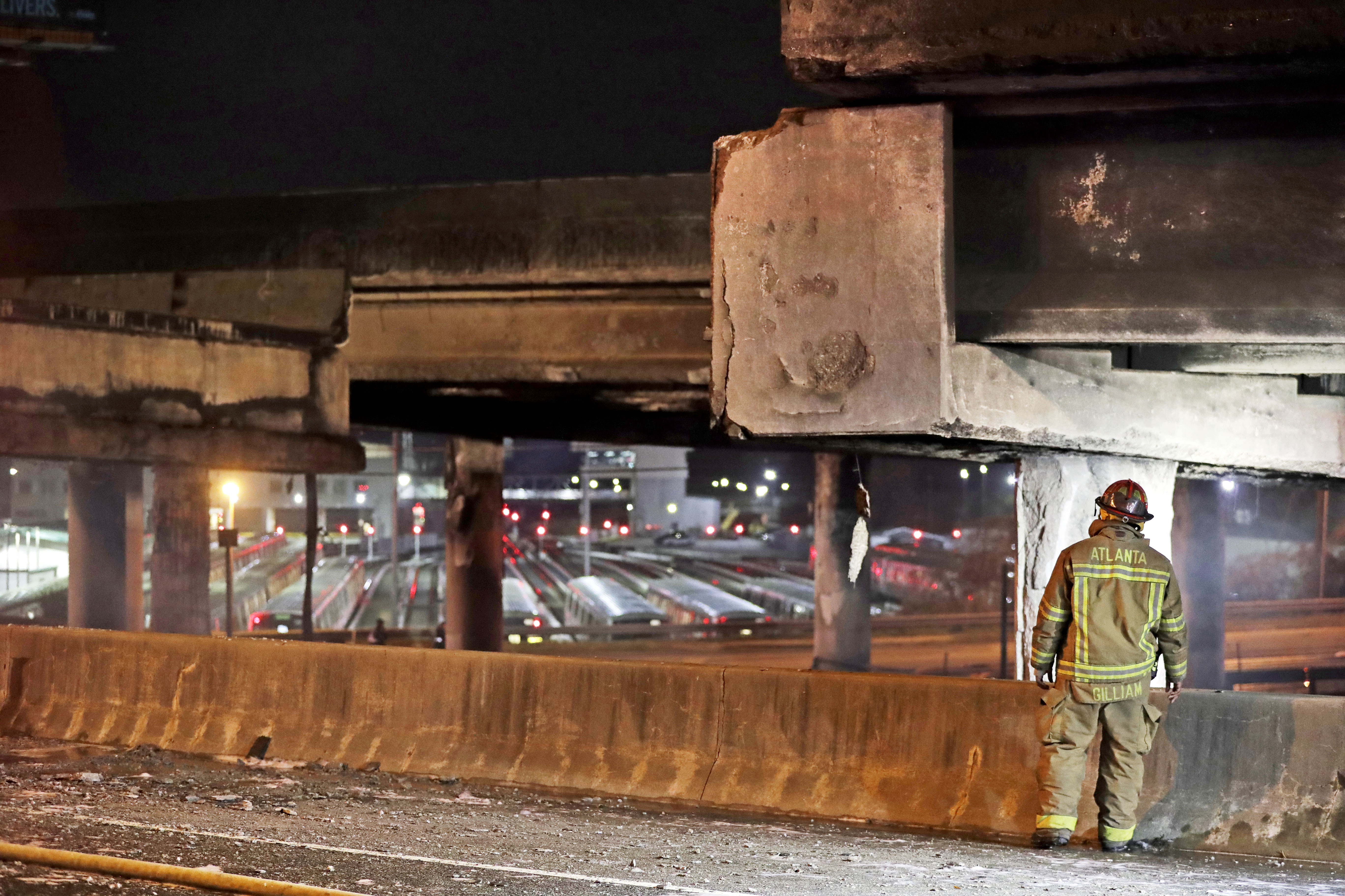 A firefighter surveys the section of an overpass that collapsed from a large fire on Interstate 85 in Atlanta, March 30, 2017.