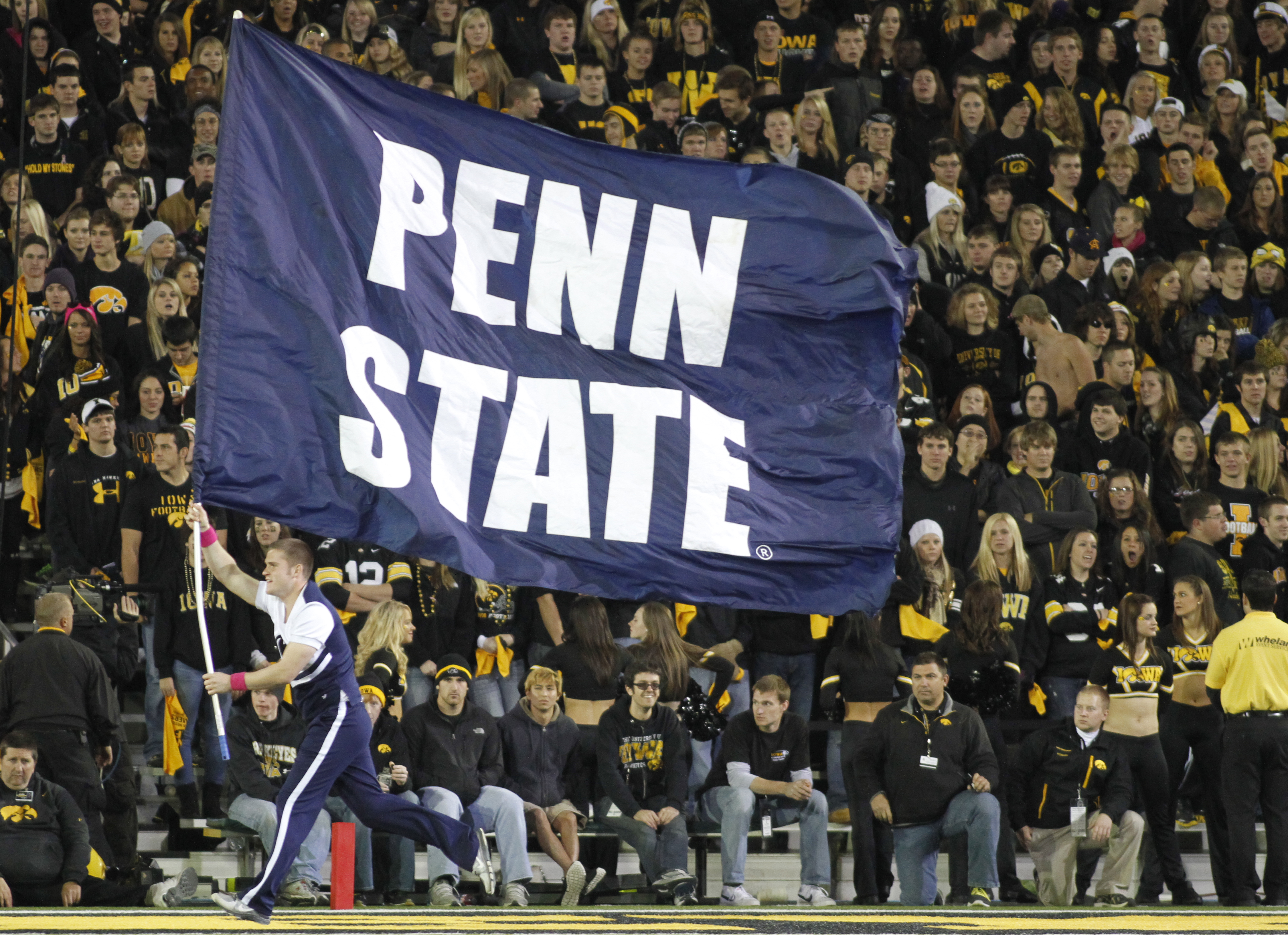 A cheerleader of the Penn State Nittany Lions carries a banner through the endzone to celebrate a touchdown against the Iowa Hawkeyes on October 20, 2012 at Kinnick Stadium in Iowa City, Iowa.