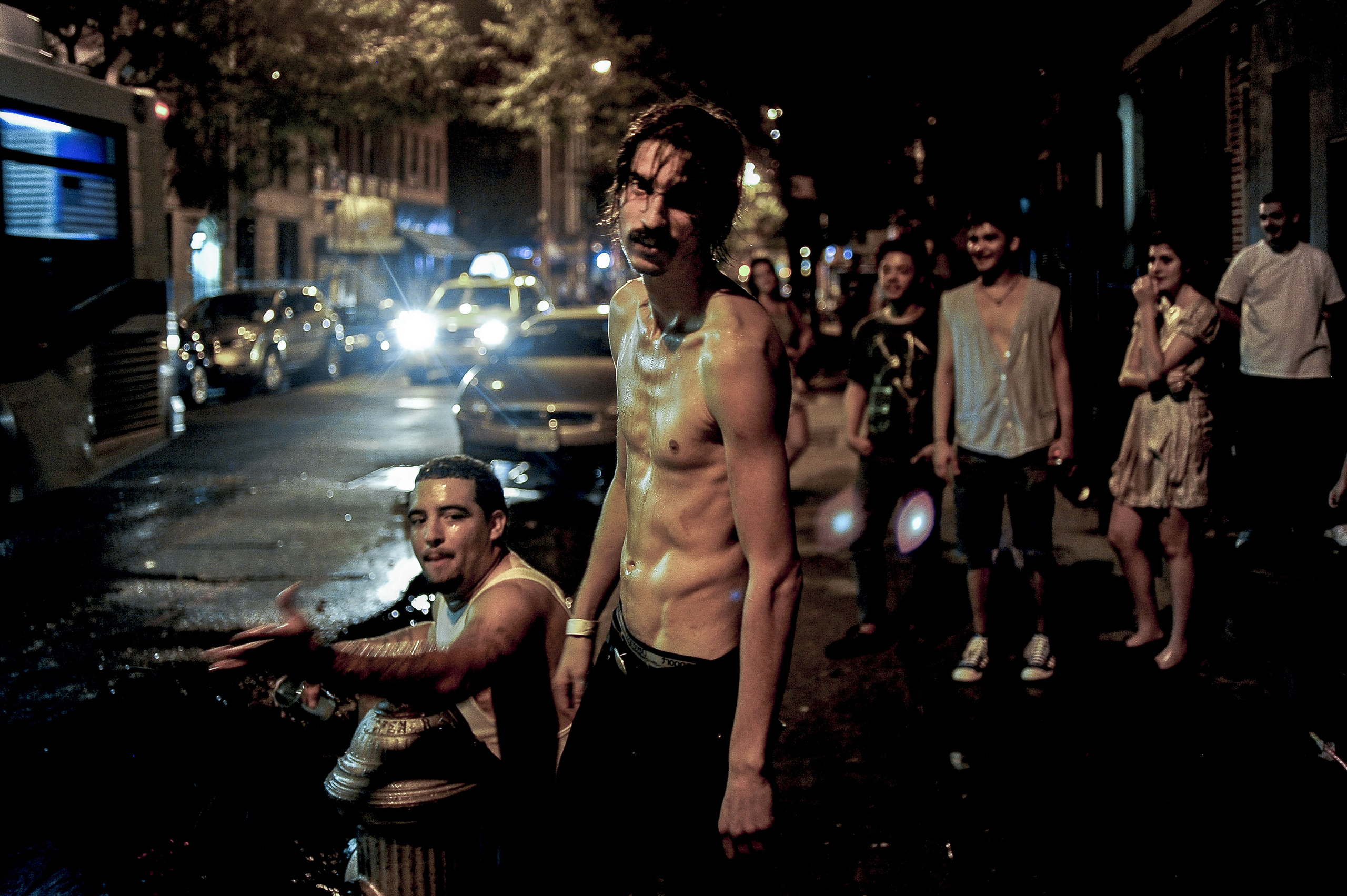 USA. Manhattan, New York. 2010. Playing in a busted fire hydrant on the 4th of July.