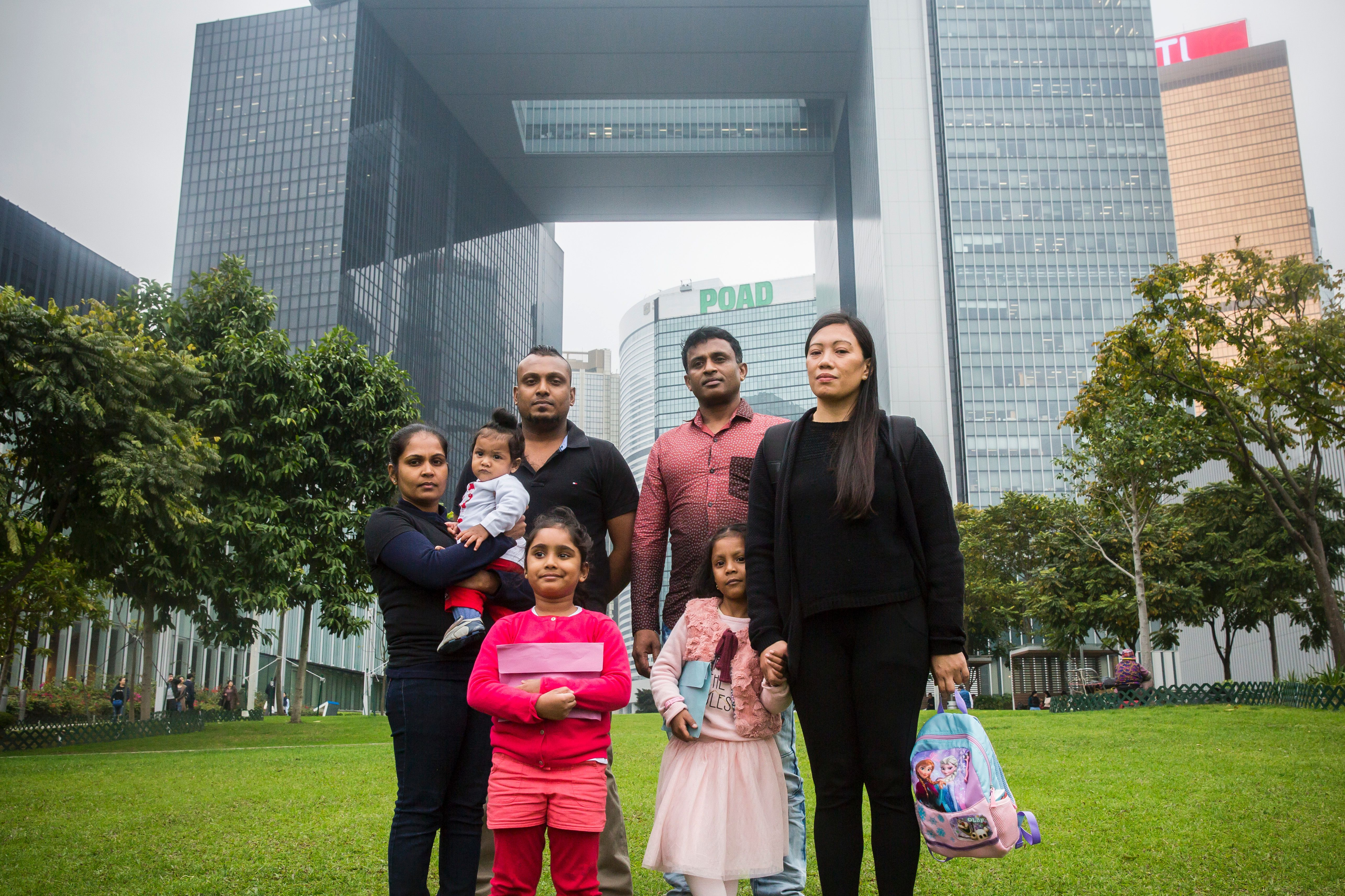 Sri Lankan refugee Supun Thilina Kellapatha (3rd L), 32, his partner Nadeeka (L), 33, with their baby boy Dinath, daughter Sethumdi, 5, Sri Lankan refugee Ajith Puspa (3rd R), 45, and Filipino refugee Vanessa Rodel (R), 40, with her daughter Keana, 5, pose for a photo in front of the government buildings of Hong Kong on Feb. 23, 2017, after attending a press conference where they said Sri Lankan Criminal Investigation Division (CID) is searching for them.