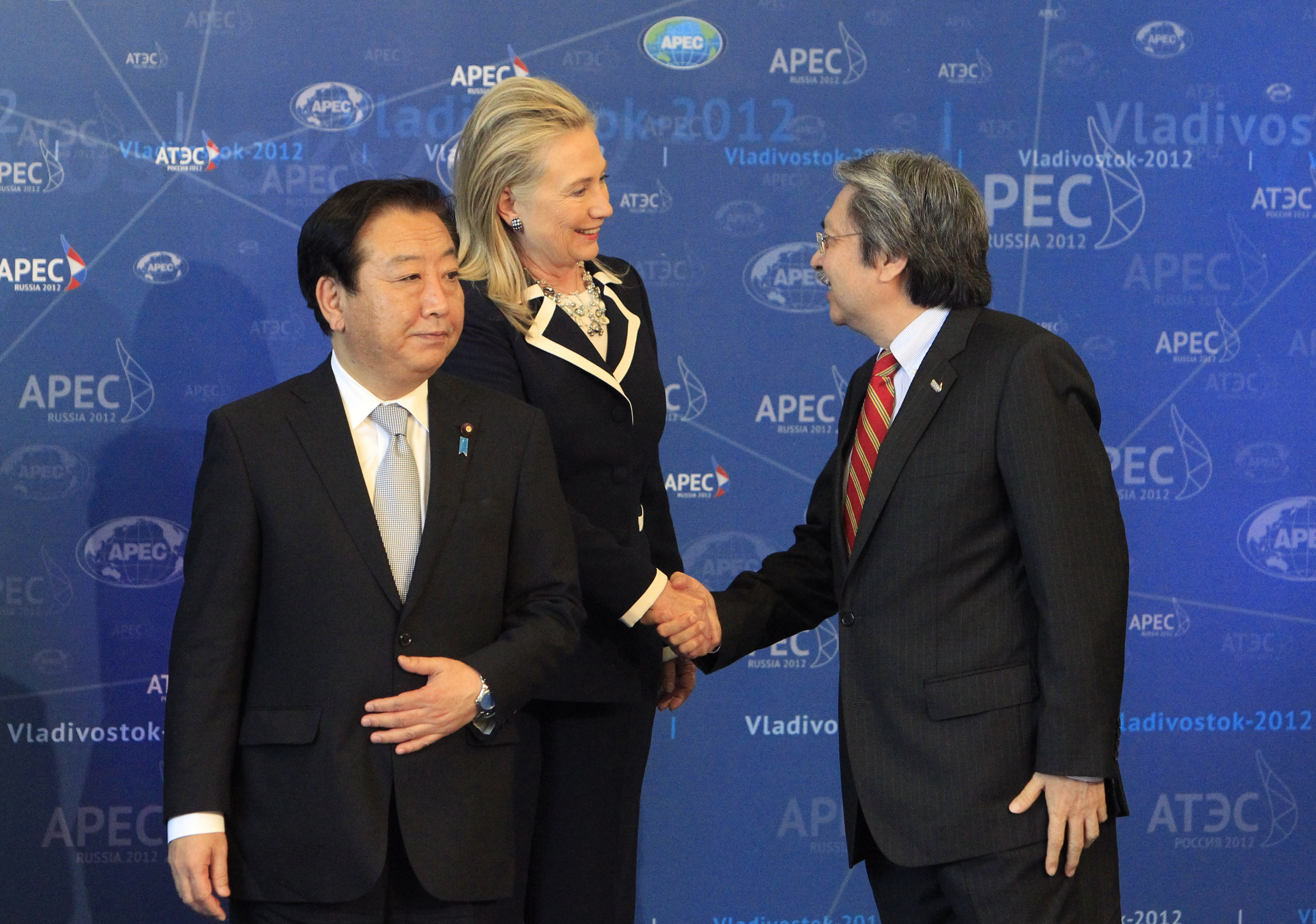 U.S. Secretary of State Hillary Clinton shakes hands with Hong Kong's Financial Secretary John Tsang as Japan's Prime Minister Yoshihiko Noda looks on at the Asia-Pacific Economic Cooperation Summit in Vladivostok, Russia, on Sept. 9, 2012