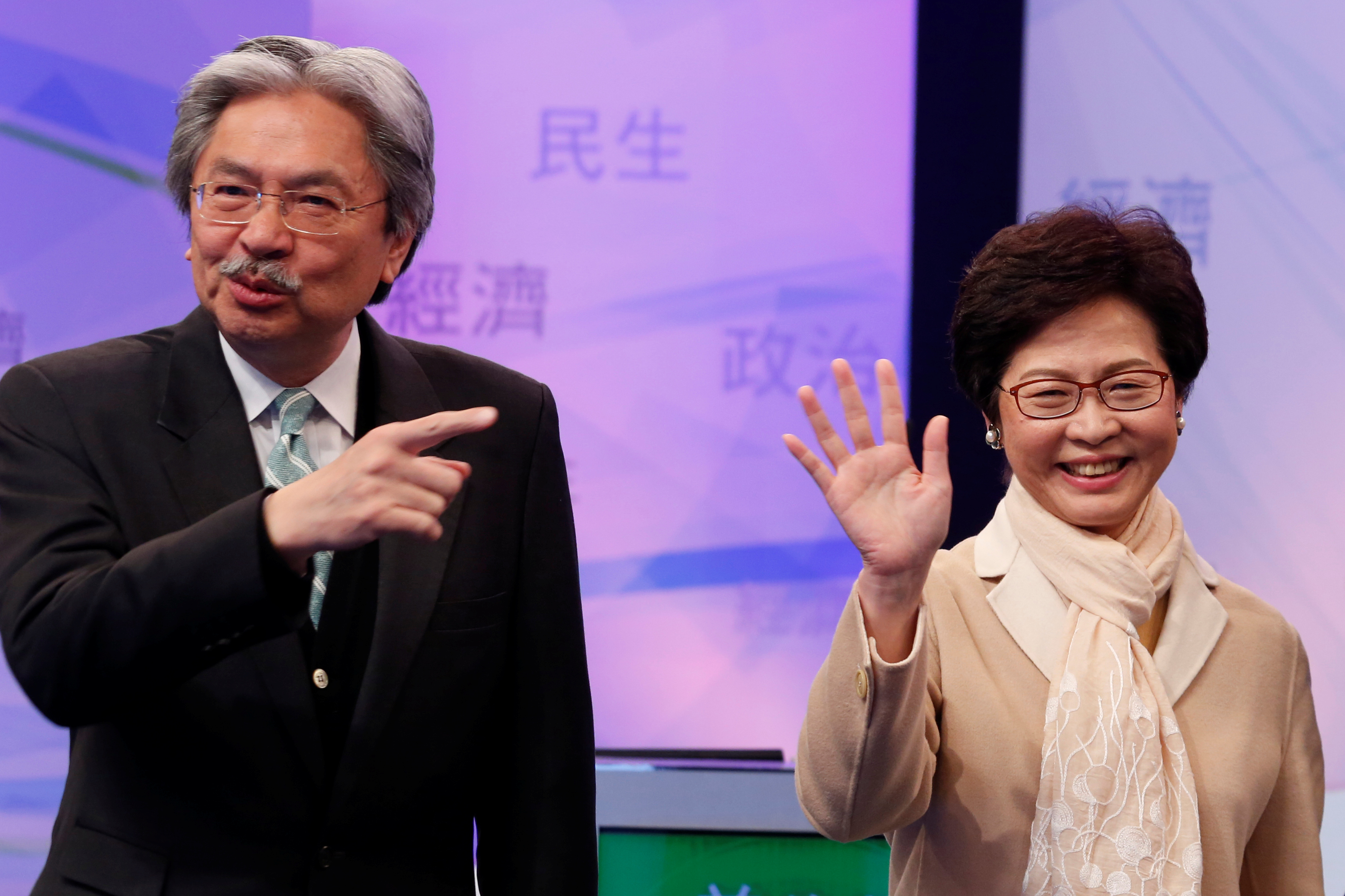 Chief Executive candidates, former Financial Secretary John Tsang and former Chief Secretary Carrie Lam, react before a debate in Hong Kong on March 14, 2017