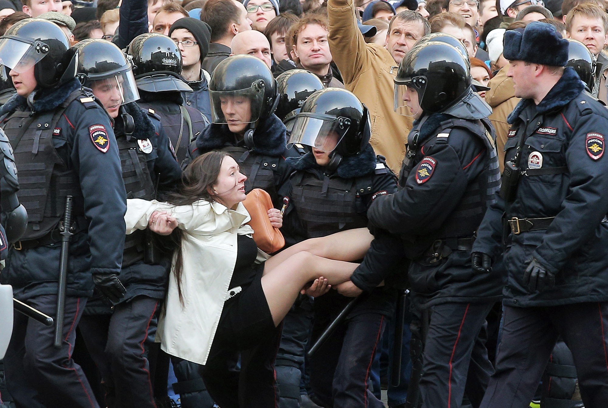 Police officers detain a demonstrator during an opposition rally in Moscow on March 26, 2017.