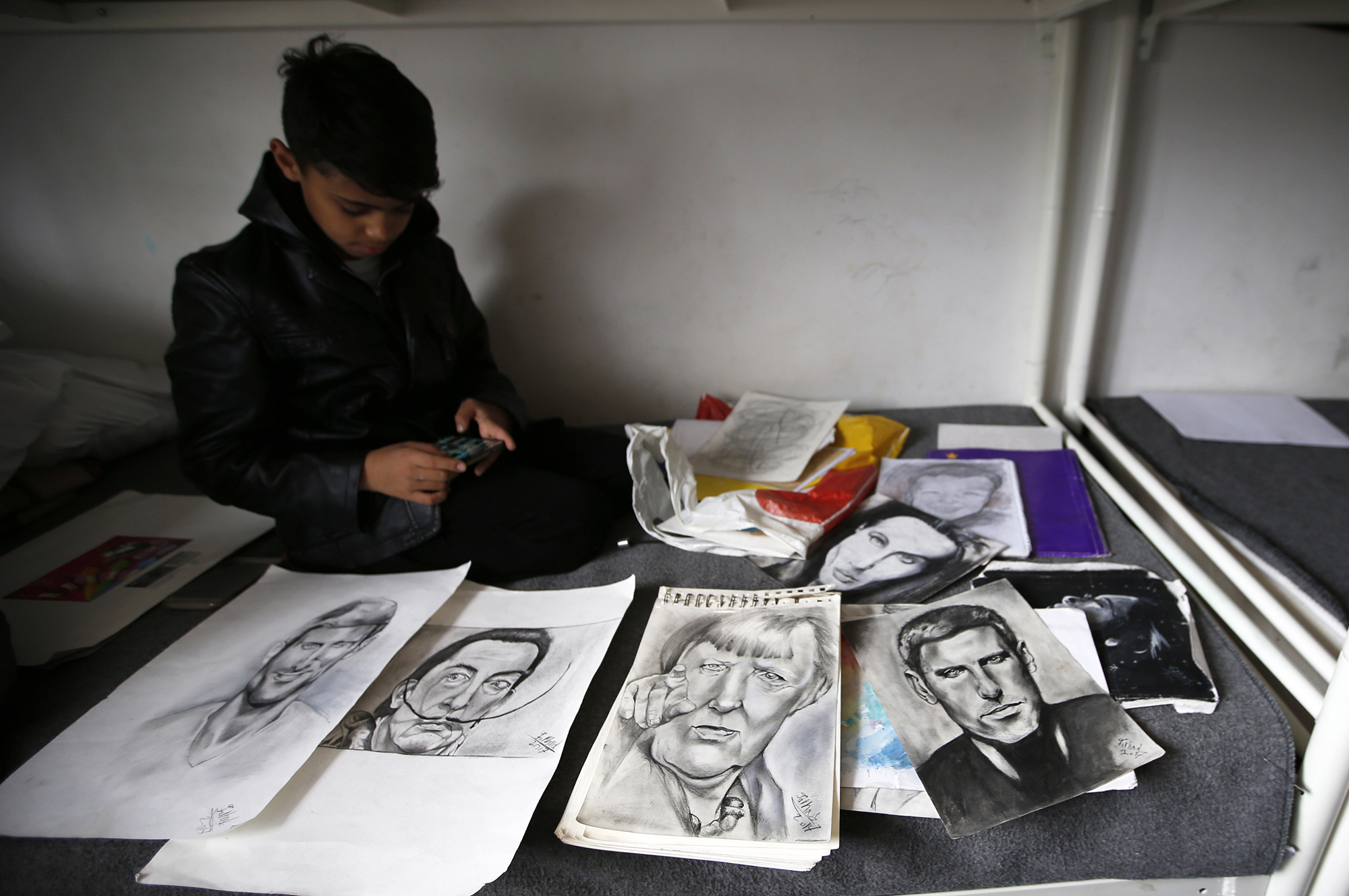 Farhad Nouri sits on a bed by a portrait of Serbian tennis player Novak Djokovic, left, Spanish surrealist painter Salvador Dali, second from left, and German Chancellor Angela Merkel, third from left, in his room in the  Krnjaca  collective centre near Belgrade, Serbia, Monday, March 13, 2017.