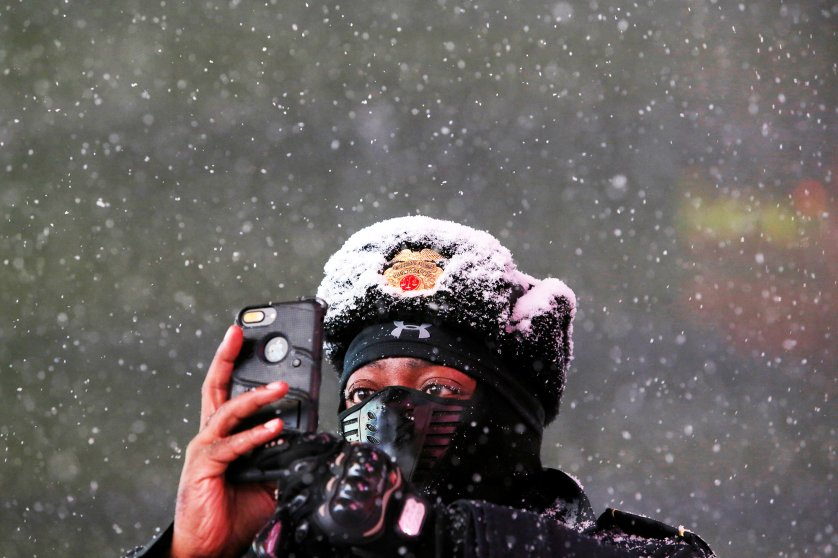 Times Square Public Safety Sergeant Baldwin Davis captures falling snow with his cellular device in Times Square in Manhattan, New York
