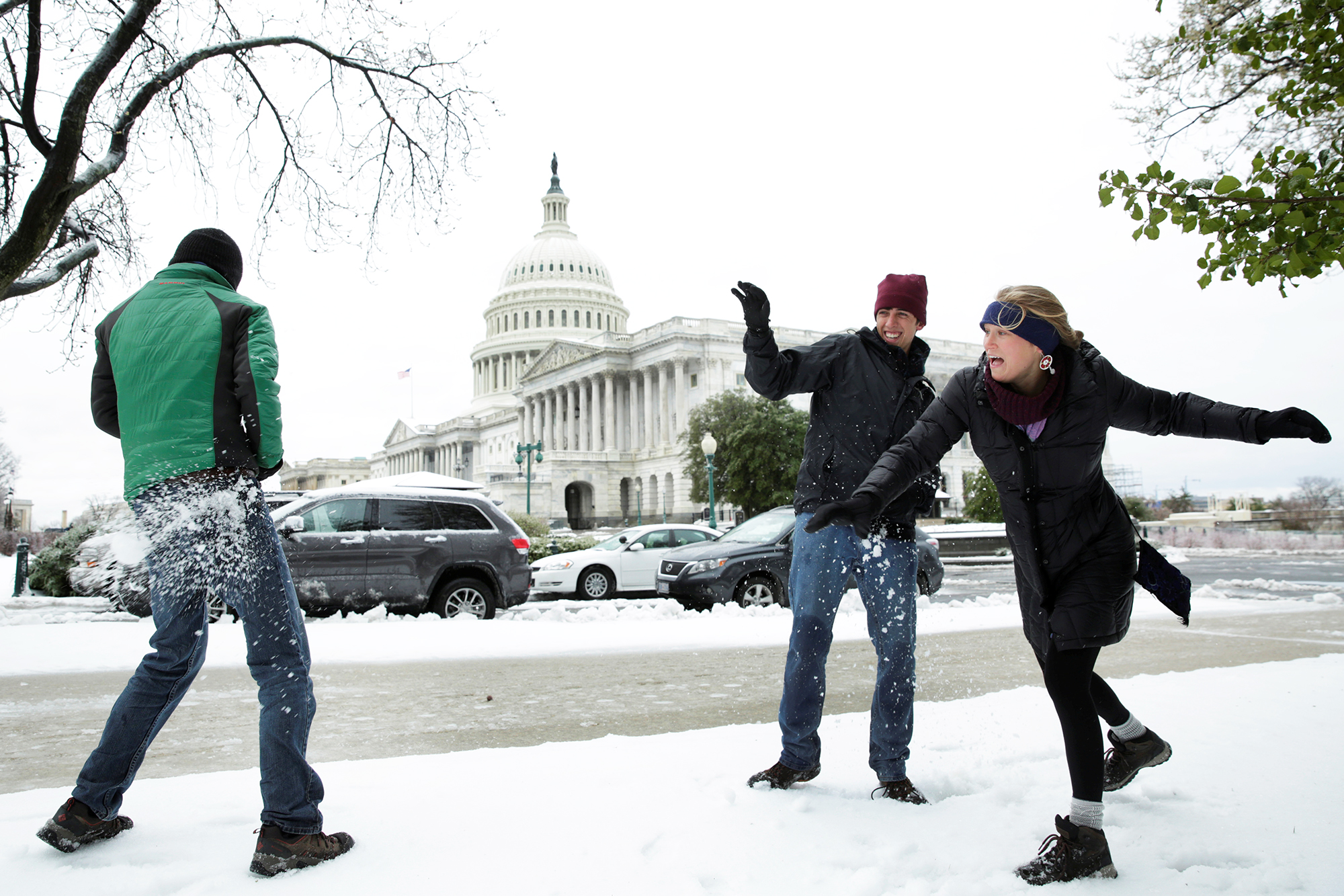 Tourists Jake Lambert, Clay Lambert and Kelsey Chaloux from Orlando, Fla. play snowball on Capitol Hill in Washington, D.C., on March 14, 2017.