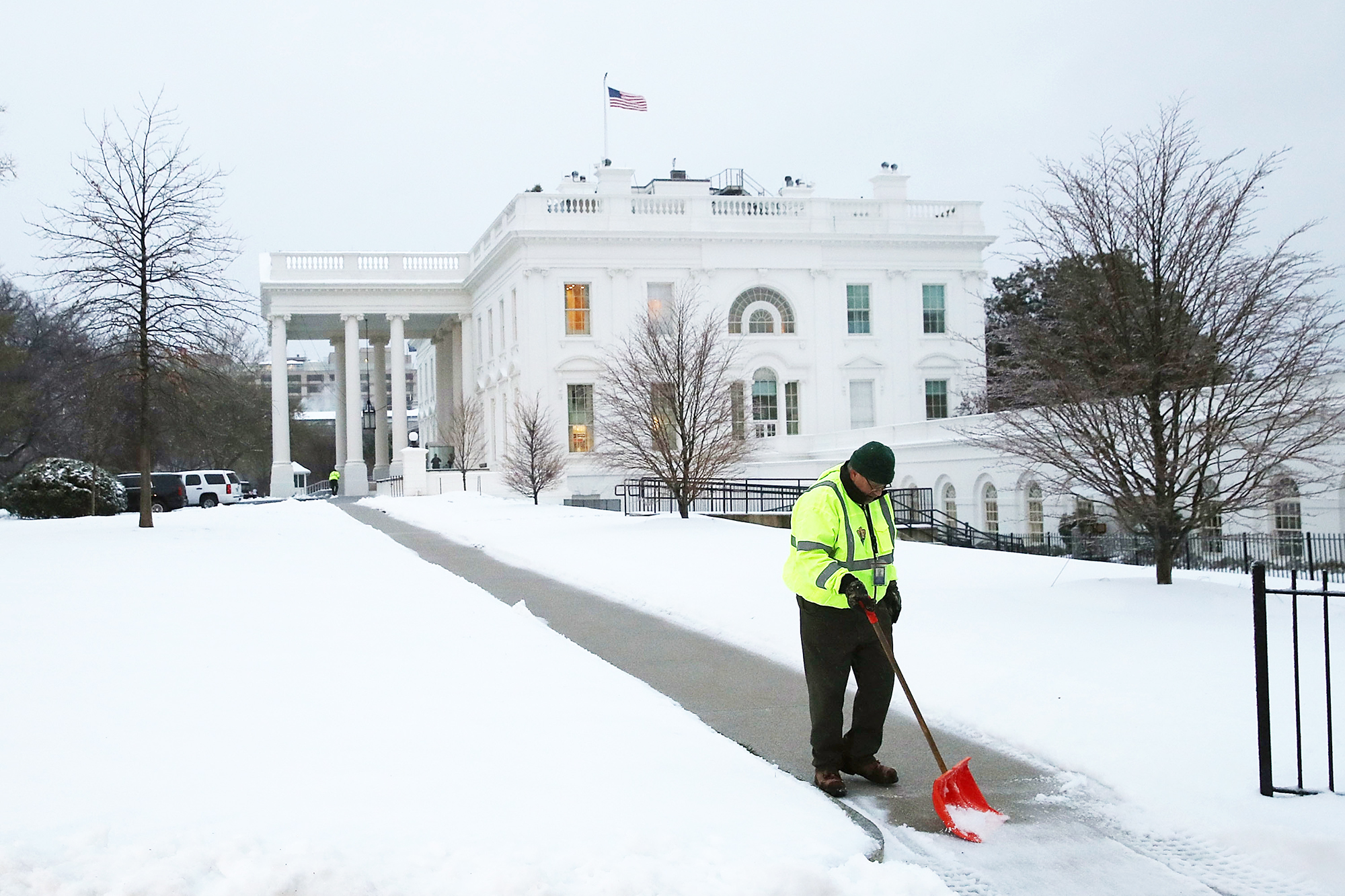A U.S. Park Service worker shovels snow off of the sidewalk at the White House in Washington, D.C., on March 14, 2017.