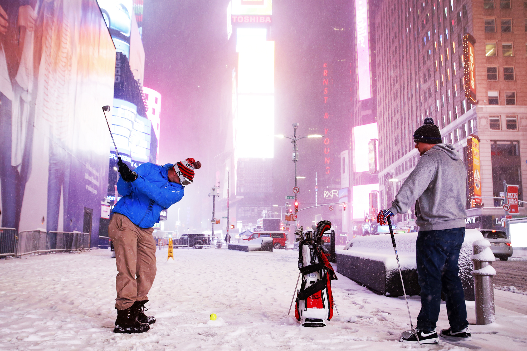 Two men play golf with a tennis ball as Winter Storm Stella sweeps through Times Square in New York City, on March 14, 2017.