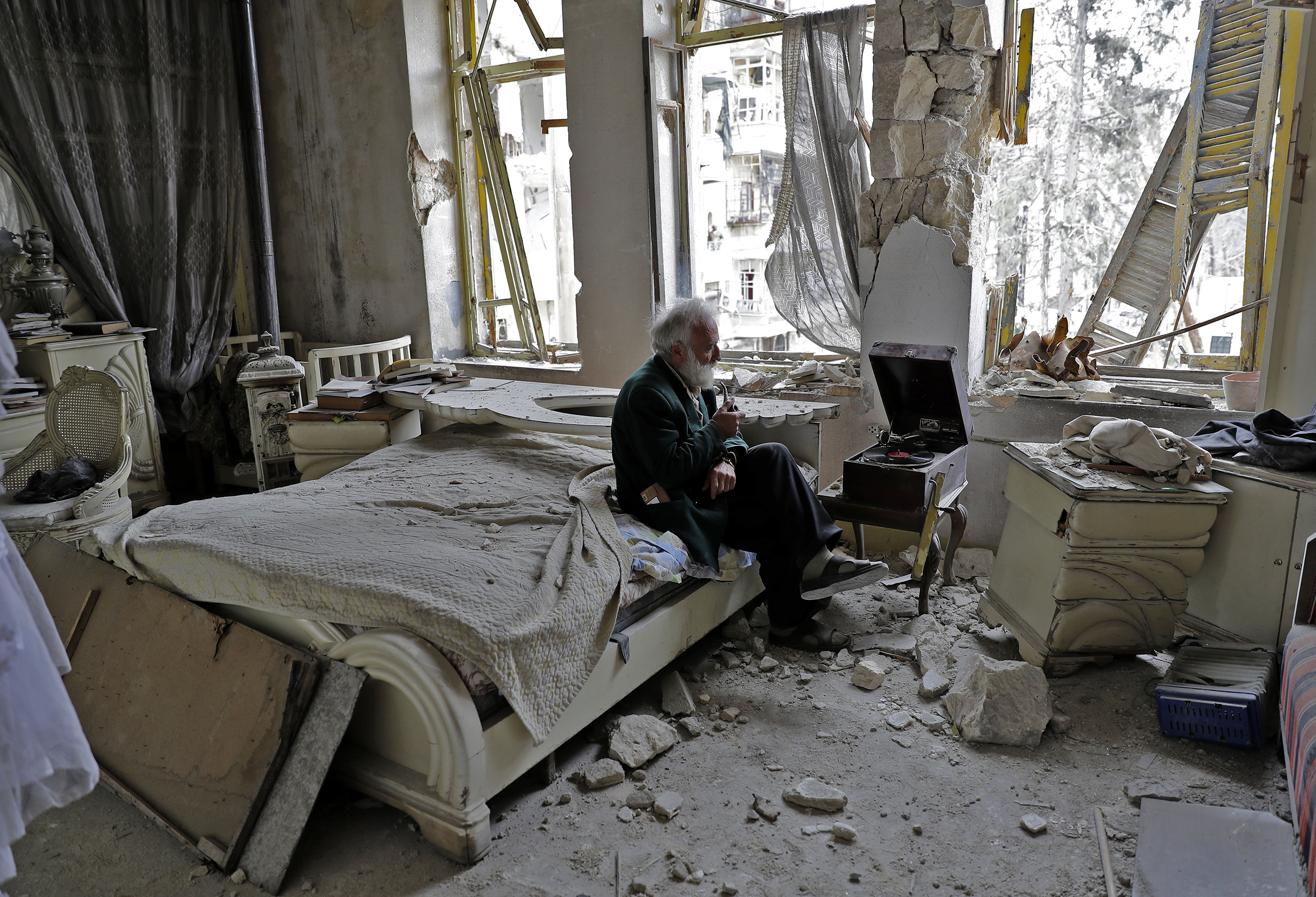 """The typical photo depicting the people surviving war it was not. People widely circulated this haunting March photo of  Abu Omar, 70, and his pipe as he listened to his record player from his seat on his broken bed amid the rubble in Aleppo where he insisted on staying.  As for the portrait's spread, the photographer Joseph Eid will tell you """"this picture touches the soul of the human being."""""""