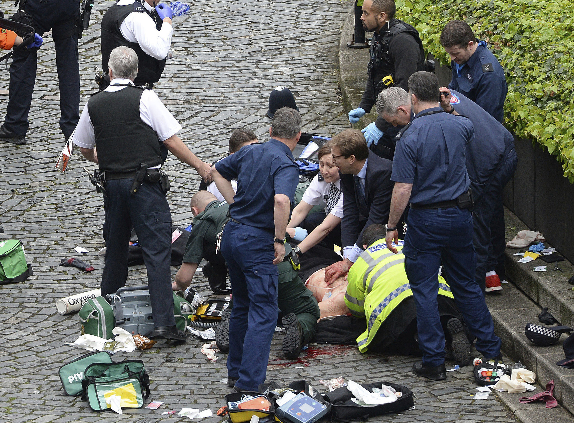 Conservative Member of Parliament Tobias Ellwood, centre, helps emergency services attend to an injured person outside the Houses of Parliament, London on March 22, 2017.