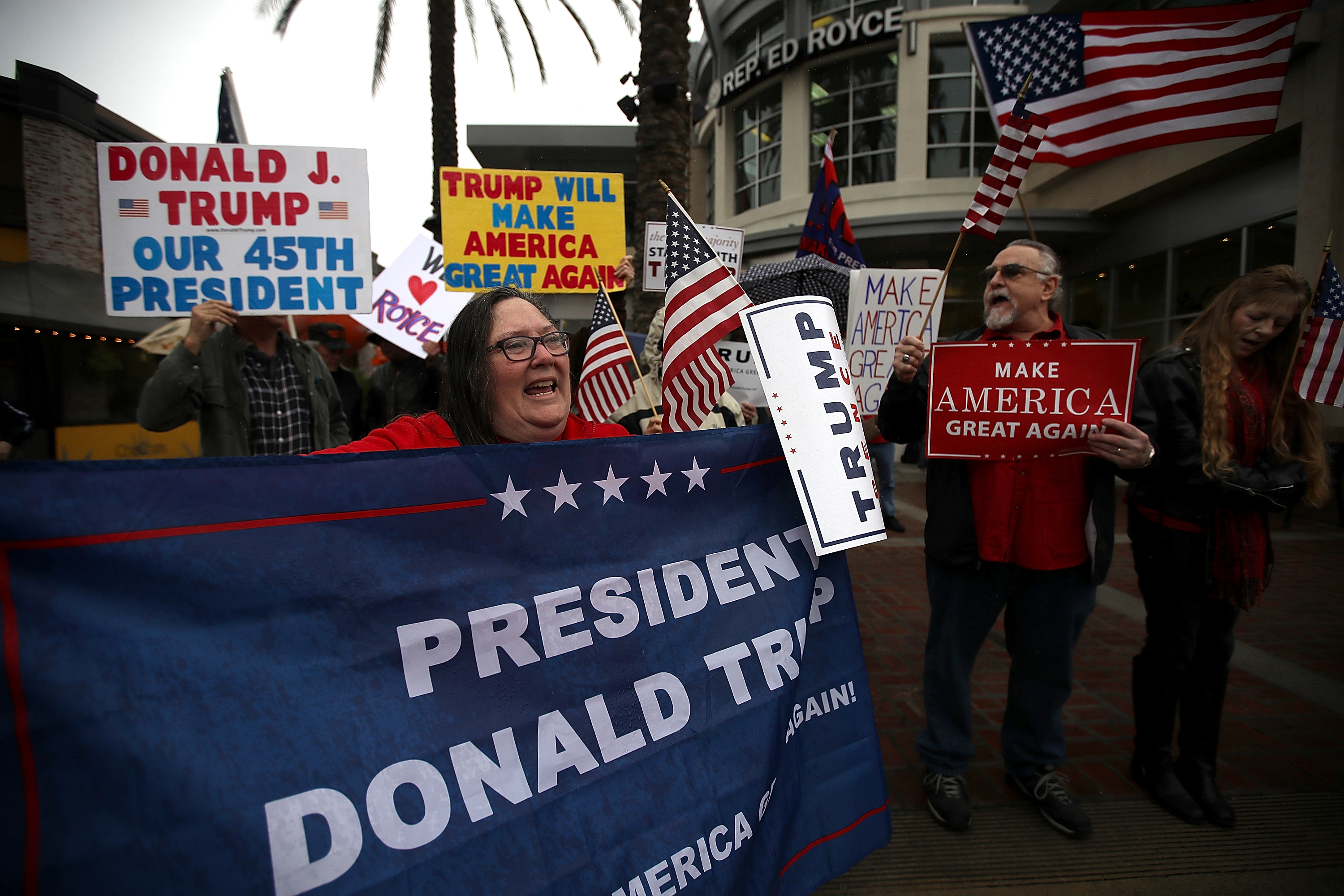 Supporters of U.S. President Donald Trump hold signs during a rally in favor of the  America First  agenda on February 27, 2017 in Brea, California.