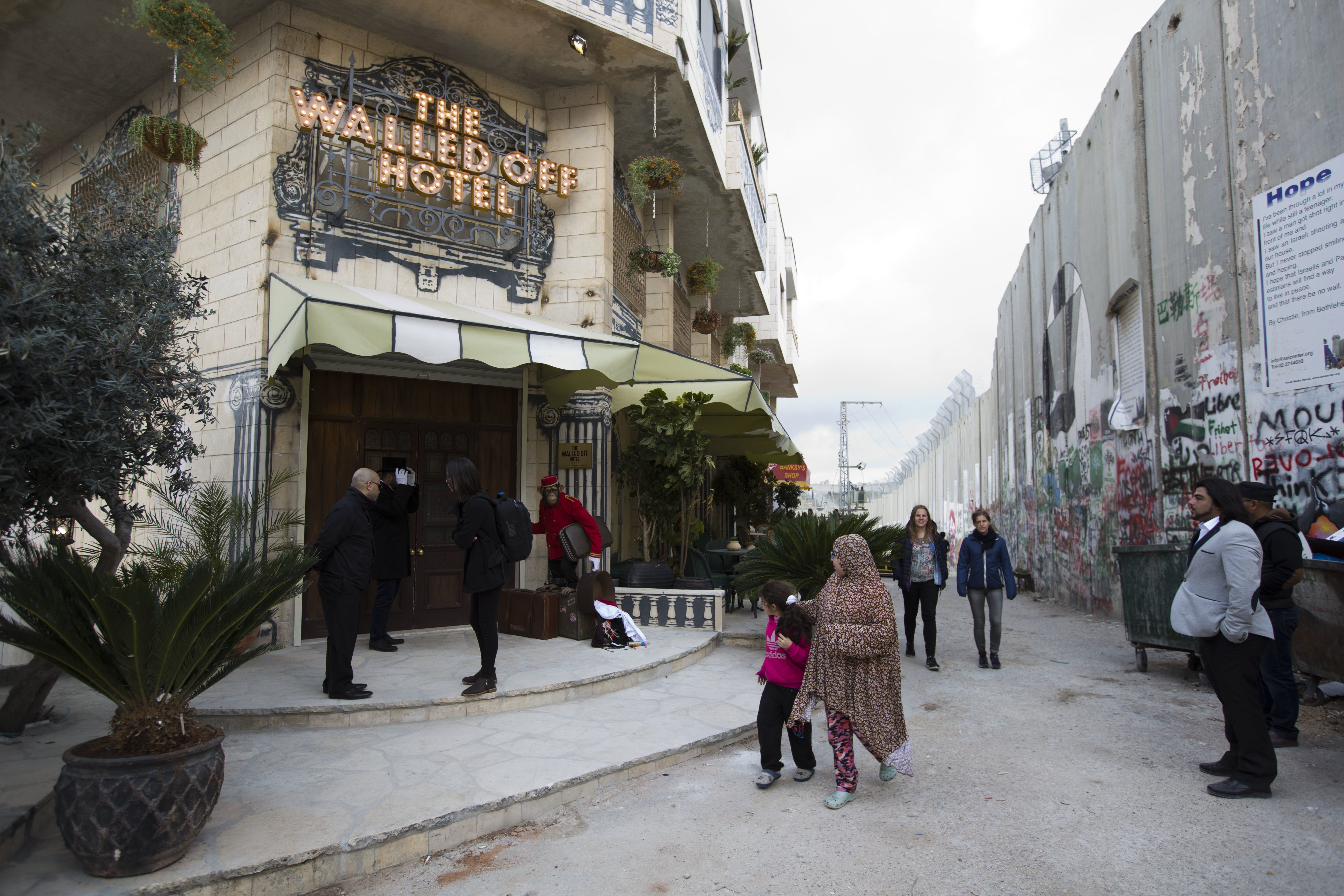 People pass by the  The Walled Off Hotel  and the Israeli security barrier in the West Bank city of Bethlehem, on March 3, 2017.