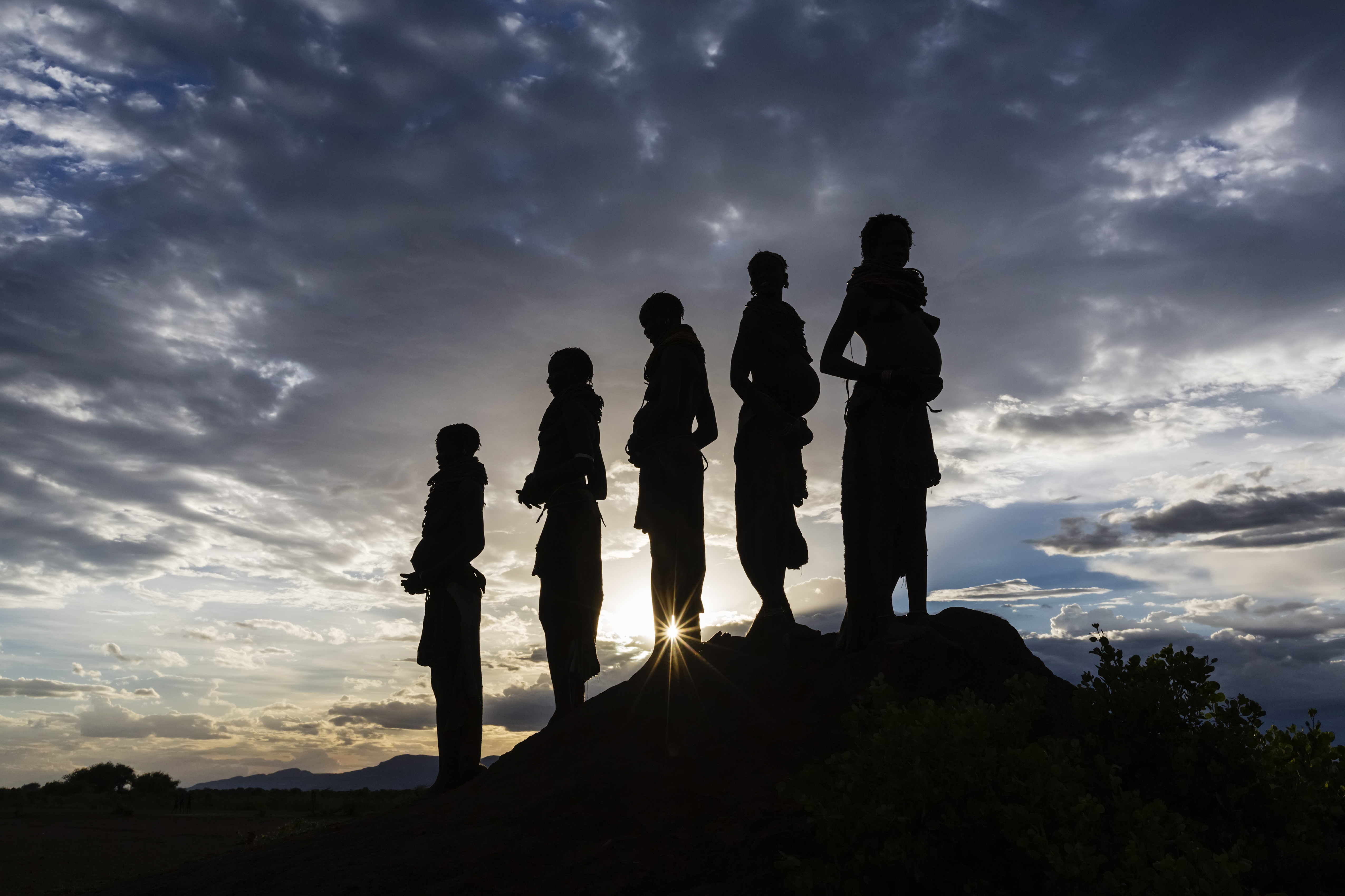Silhouettes of pregnant woman under cloudy sky at sunset, Nyangaton, Ethiopia