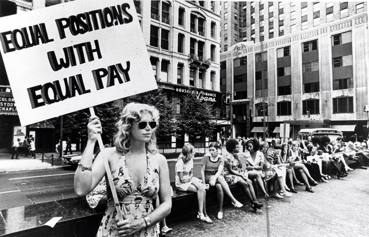 A lone woman stands on a corner protesting unequal pay for women in an unidentified section of Cincinnati, Ohio, ca.1970s. (Photo by Cincinnati Museum Center/Getty Images)