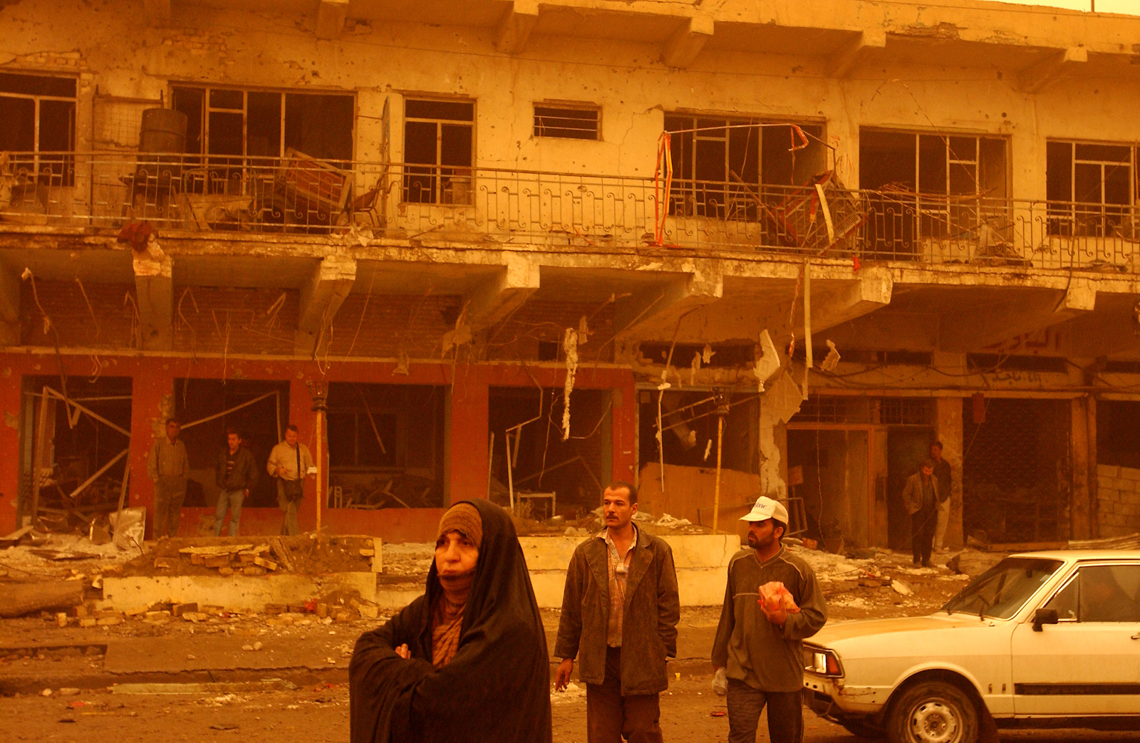During a sandstorm, Iraqis stand in front of wreckage of a building in the days following the U.S. bombing campaign, Baghdad, Iraq, March 26, 2003.