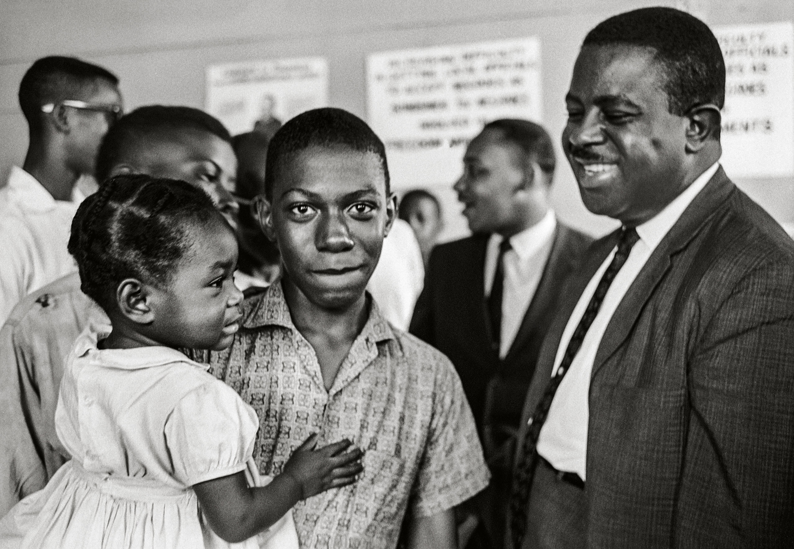 Never Published.                       The first time I photographed Dr. King,                      says Steve Schapiro,  I was not aware that                     he was going to be one of the most important people of our time.  In fact, Schapiro barely noticed him in the                     background when capturing this never-before-                     published image of Reverend Ralph Abernathy, Dr. King's best friend and advisor in Clarksdale, Mississippi,                     1963.