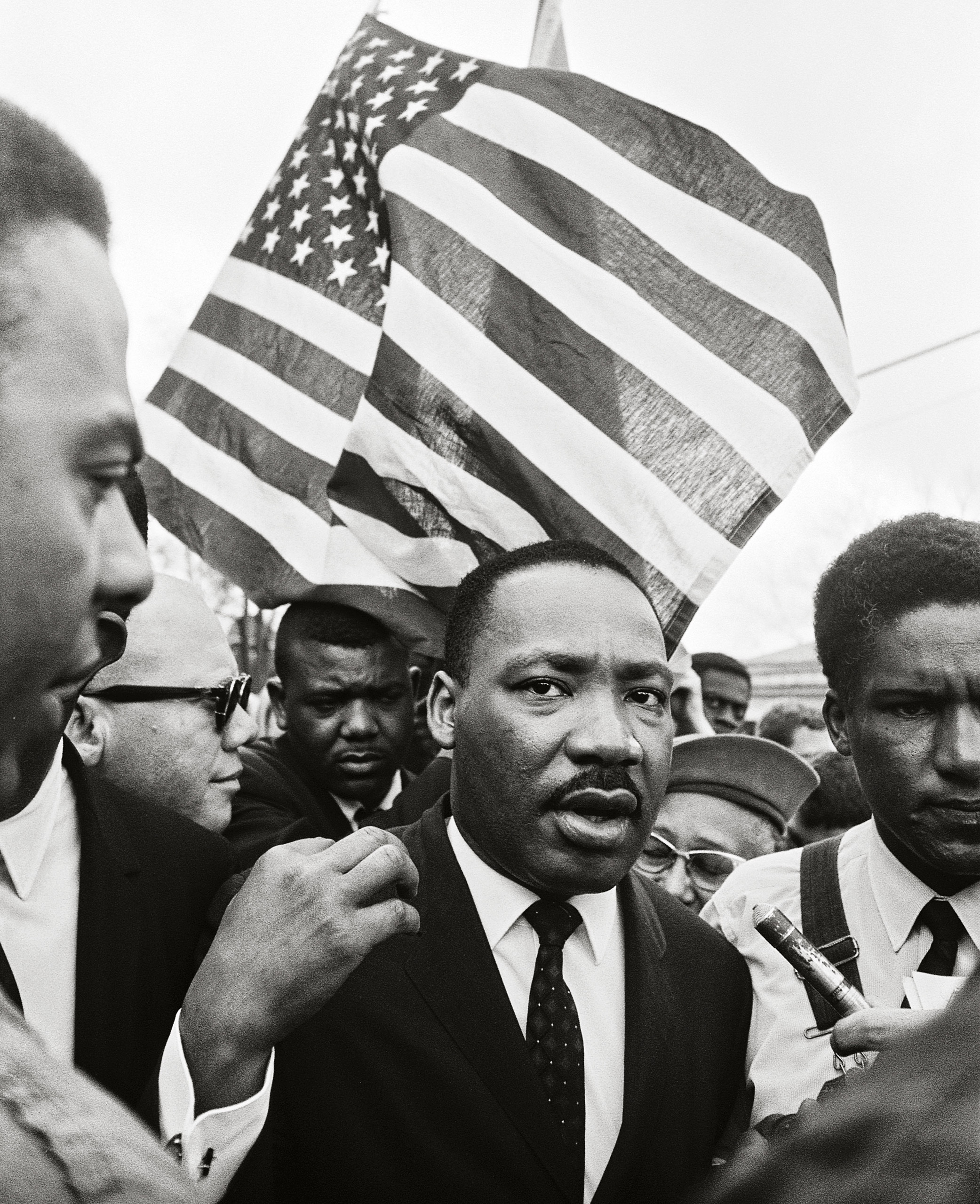 Previously Published.                               Ralph Abernathy (rear) and Dr. King lead the way on the road to Montgomery. The                               American flag was a natural symbol for a                               movement that called on the nation to live up to its principles. 1965