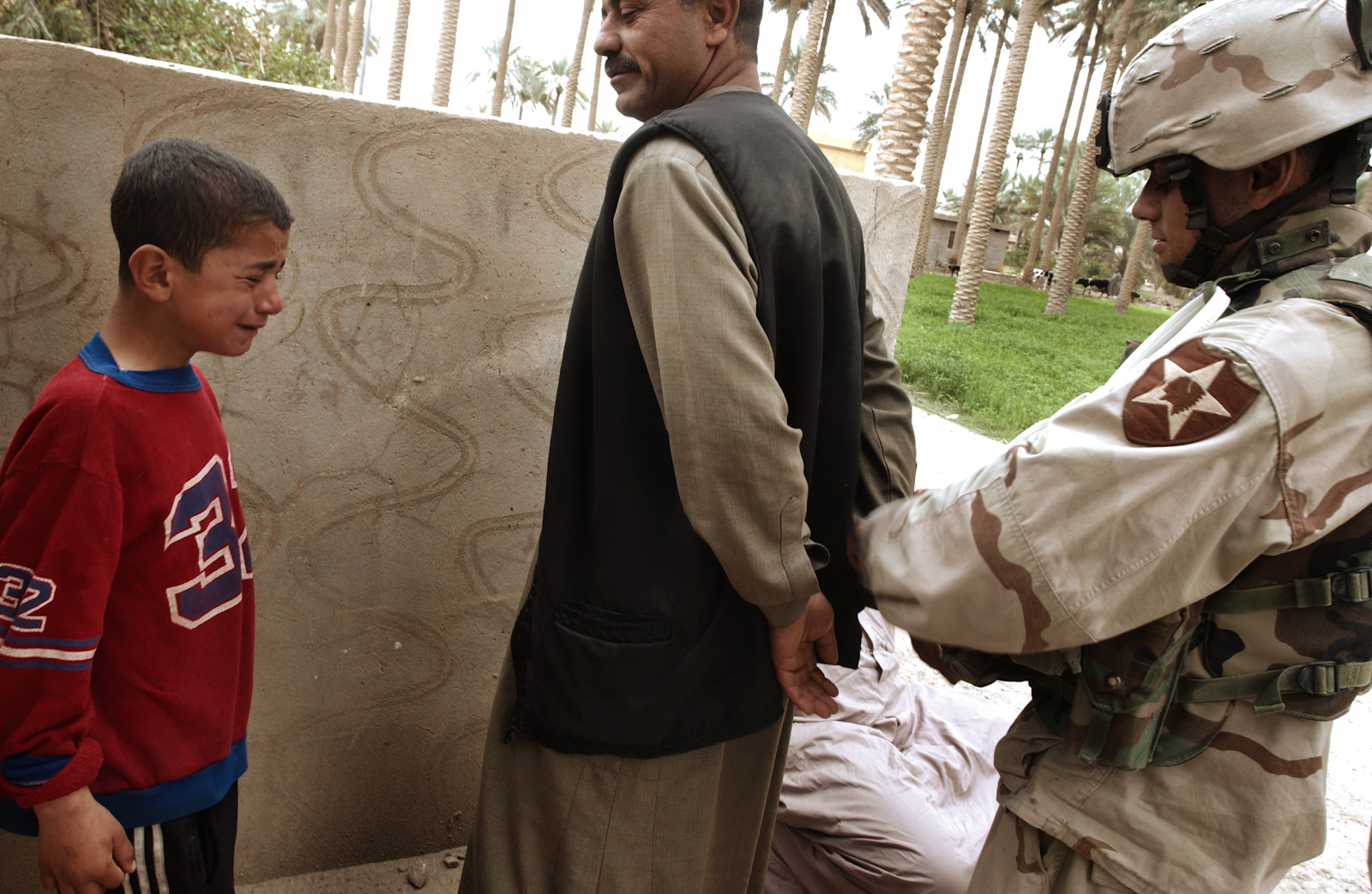 During a house to house search for insurgents in Ramadi, a boy cries as his father is taken away by U.S. soldiers, March 7, 2005.