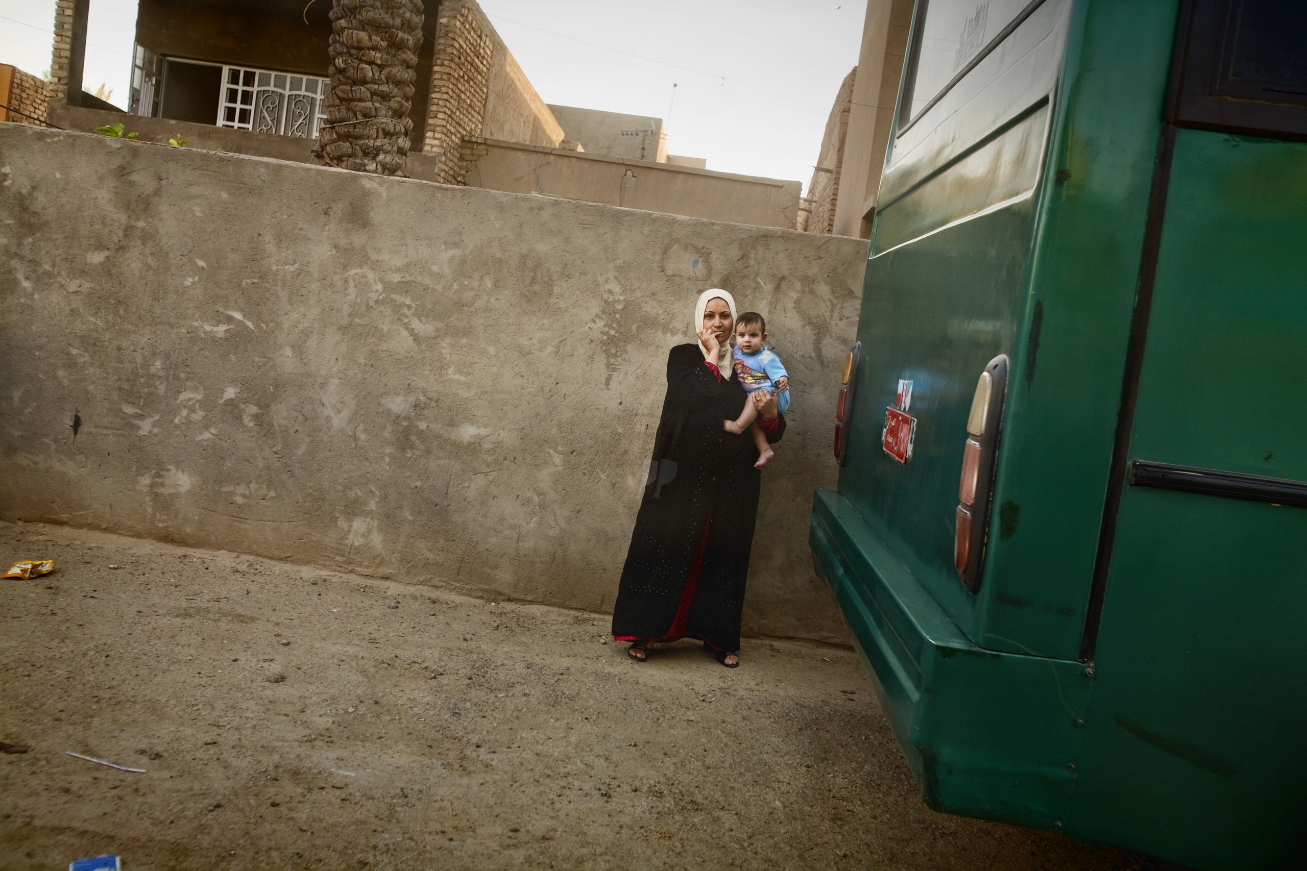A woman holds her child outside her home in the al Doura district of Baghdad, Iraq, June 5, 2007. As sectarian tensions increased, life in Doura became increasingly dangerous when Iraqi National Policemen, former members of the pro-Shiite Badr Brigades, set up a check point outside the neighborhood and began shooting Sunni civilians, including women and children.