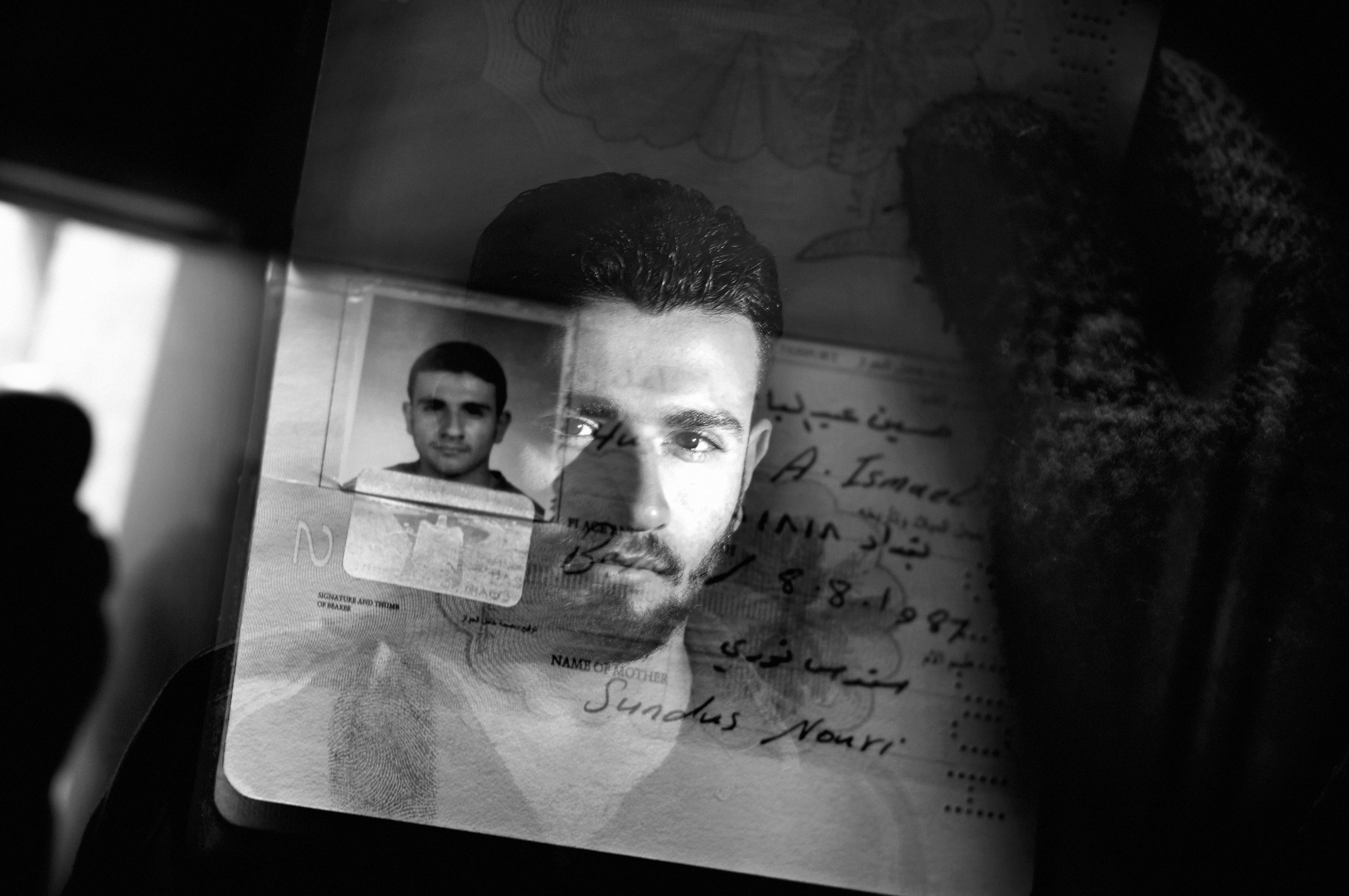 A double exposure portrait of a Sunni student with his identity card in the Sunni Adhamiya neighborhood, Baghdad, Iraq January 22, 2007.                               During the height of the civil war, as the city divided along sectarian lines, a Sunni or Shia name appearing on an identify card could result in death sentence.