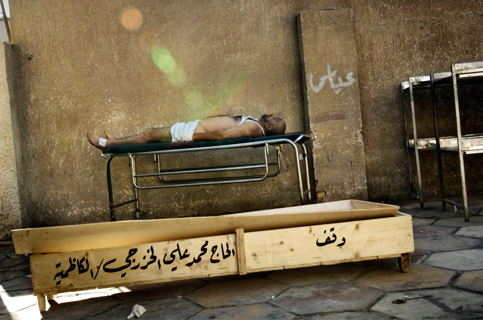 A body rests on a gurney at the Yarmouk hospital morgue in Baghdad, Iraq on July 26, 2006. People make a pilgrimage here every day in search of lost relatives that have disappeared during the night. In the previous night, 19 bodies were found in different neighborhoods throughout the city as a result of the sectarian bloodshed that is plaguing the country.