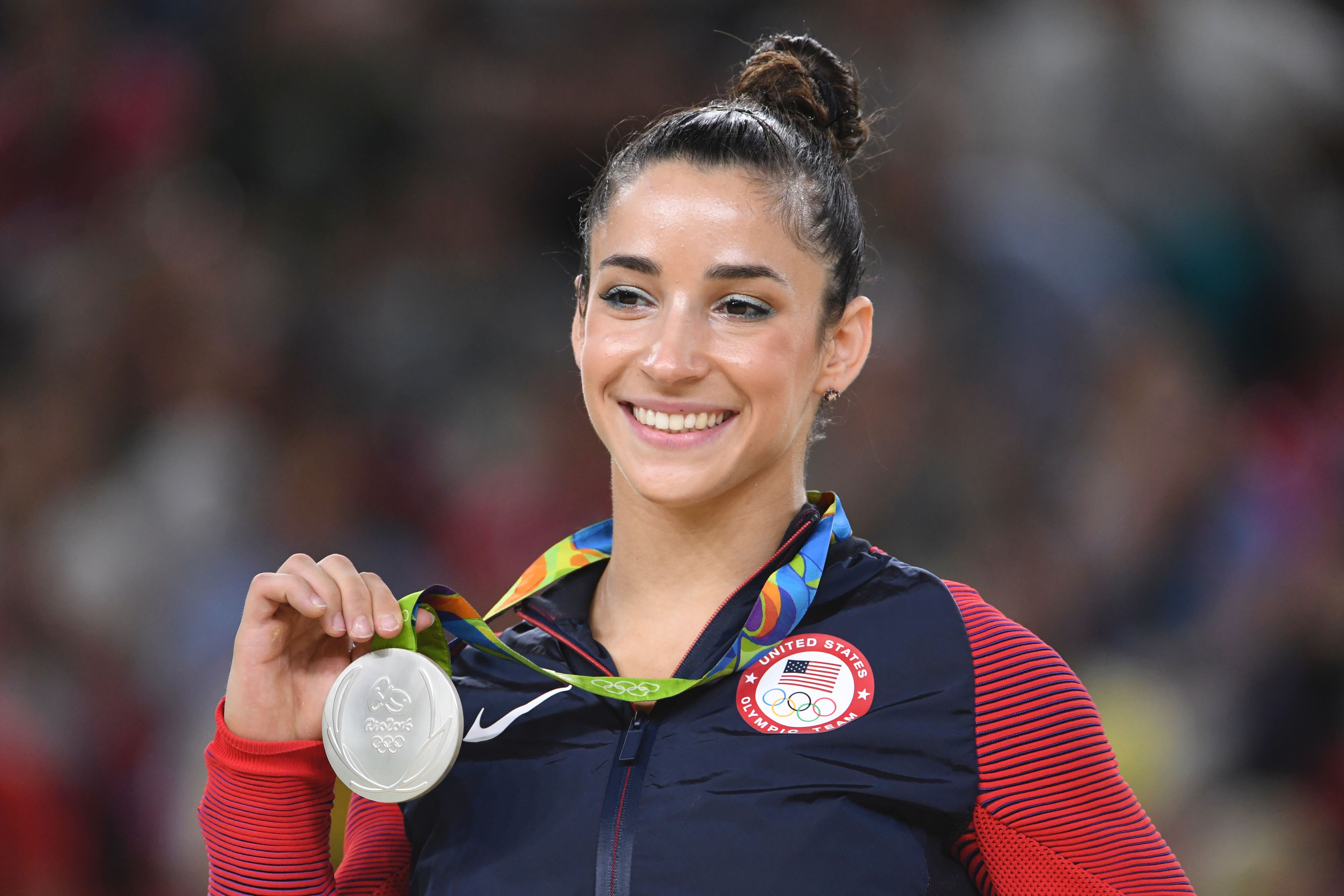 US gymnast Alexandra Raisman celebrates on the podium of the women's floor event final of the Artistic Gymnastics at the Olympic Arena during the Rio 2016 Olympic Games in Rio de Janeiro on August 16, 2016. / AFP / Toshifumi KITAMURA        (Photo credit should read TOSHIFUMI KITAMURA/AFP/Getty Images)